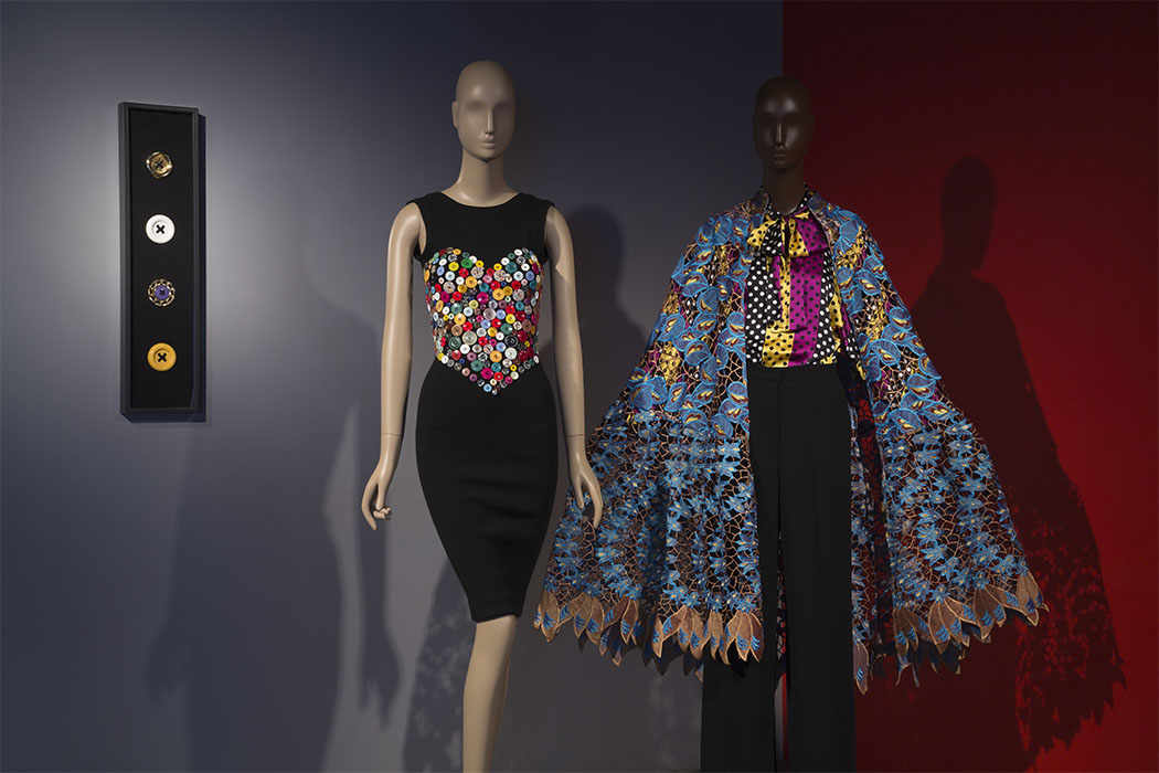 "PATRICK KELLY DRESS  (LEFT) Wool, plastic, fall 1986, USA, 2016.48.1 , museum purchase  Patrick Kelly used mismatched buttons in his designs in homage to his grandmother (""one of the chicest women I know""), who mended the Kelly family's clothing. Kelly recounted to journalist Bonnie Johnson, ""to detract from having to use mismatched buttons on his shirts, she started sewing them everywhere.""   DURO OLOWU ENSEMBLE  (RIGHT) Cotton and silk lace, silk charmeuse, wool and silk crepe, fall 2012, England, 2016.65.1, gift of Duro Olowu.  Duro Olowu's international success arises from ""a strong visual cross-cultural aesthetic, quality of the cut and the fabric, and an appreciation for the female form."" Olowu masterfully embraces bricolage, vibrantly mixing colors, prints, and textures."