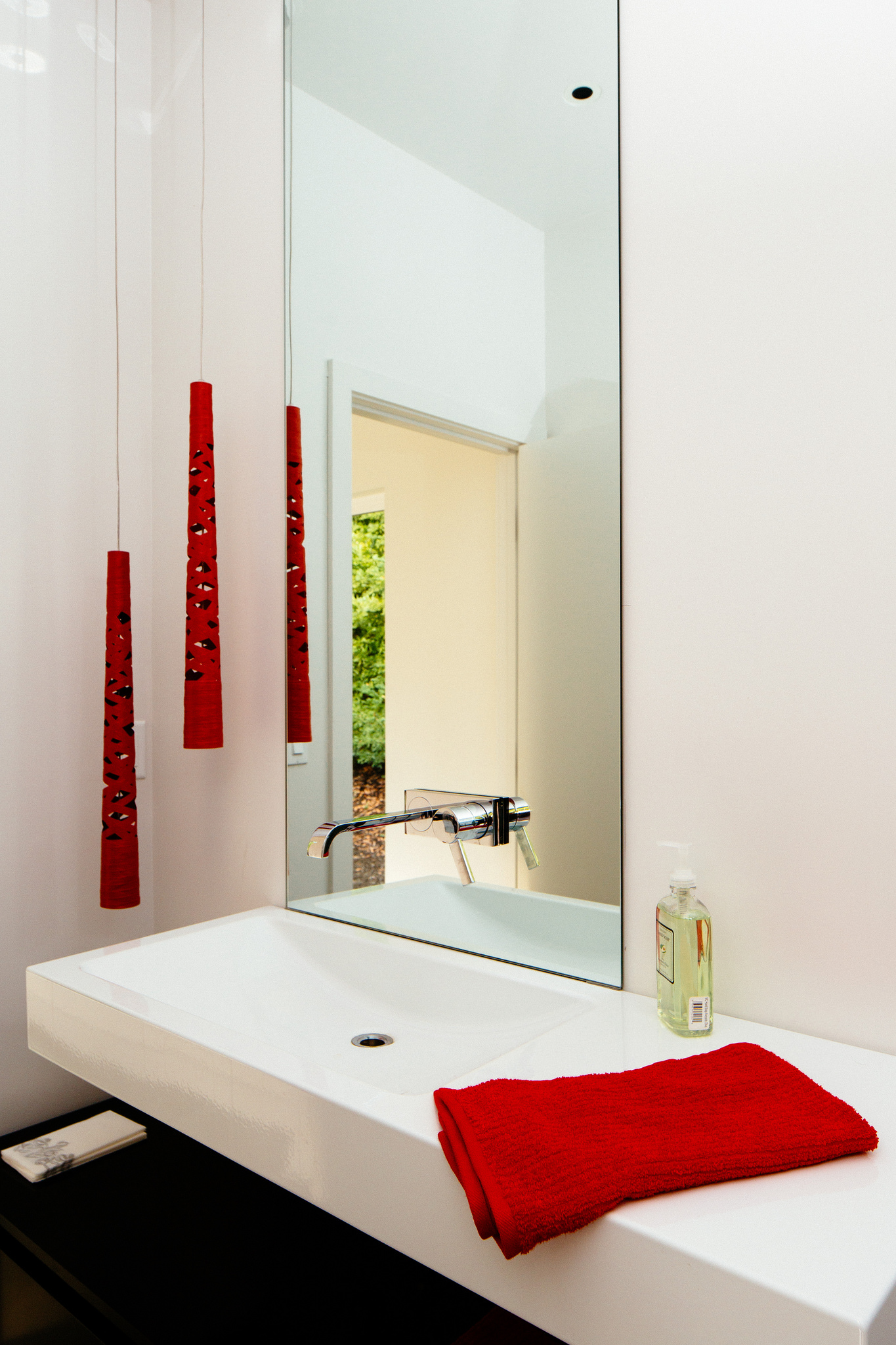 A white bathroom countertop with faucet mounted over the mirror and two small red pendants on a side