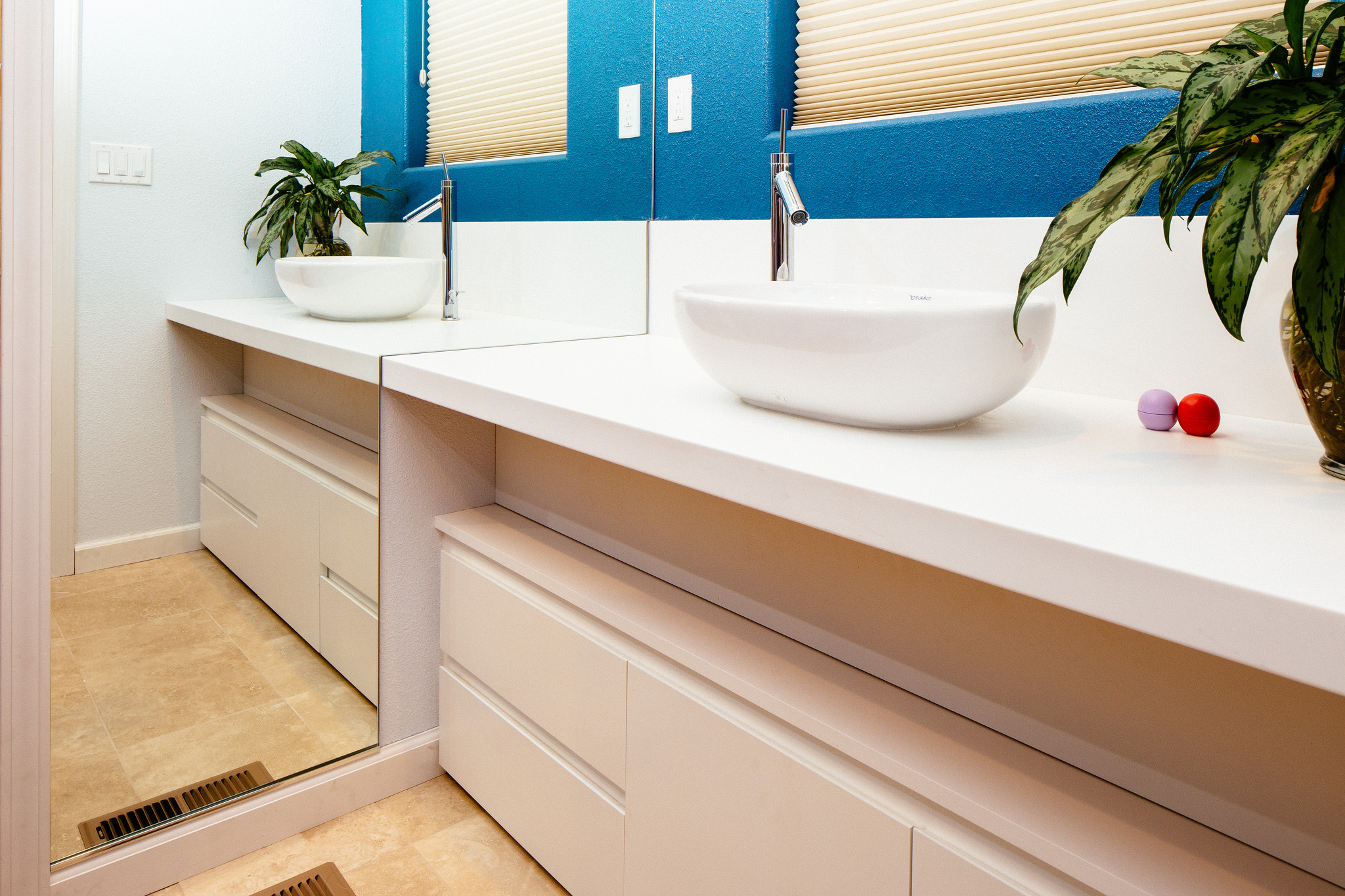 A white bathroom vanity with drawers and a sink over the white countertop.