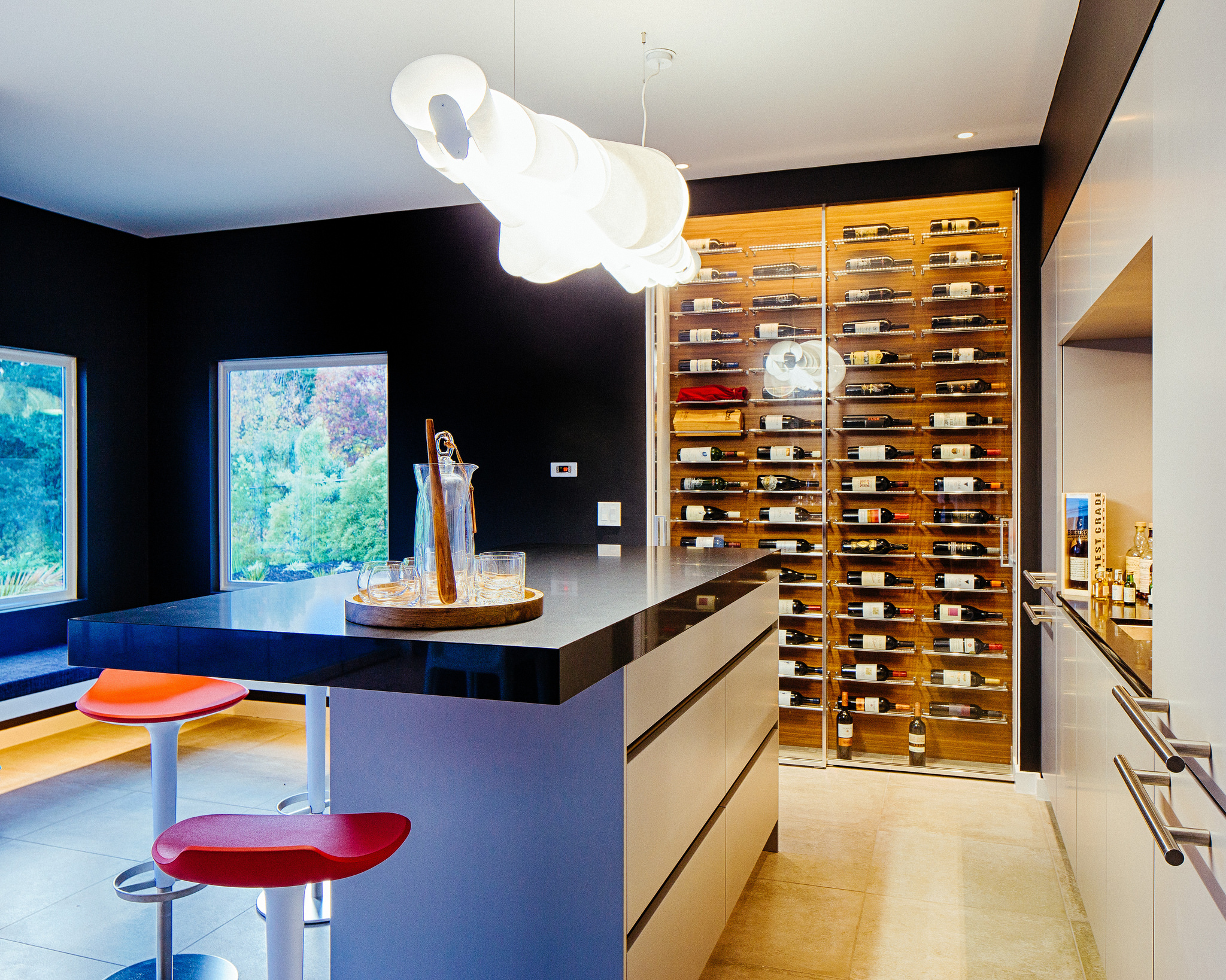 Kitchen cabinets with a grey island and a glass enclosed winecellar