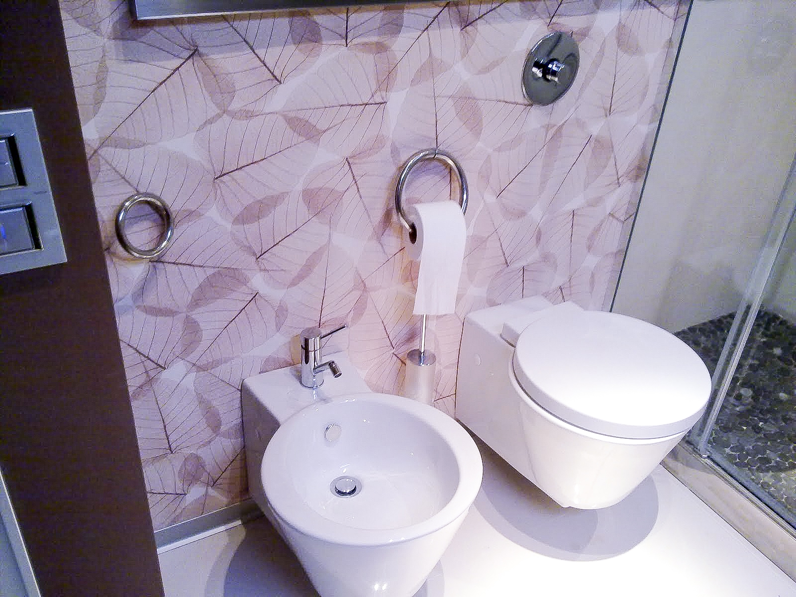 toilet and bidet wall mounted in a wall covered with wallpaper