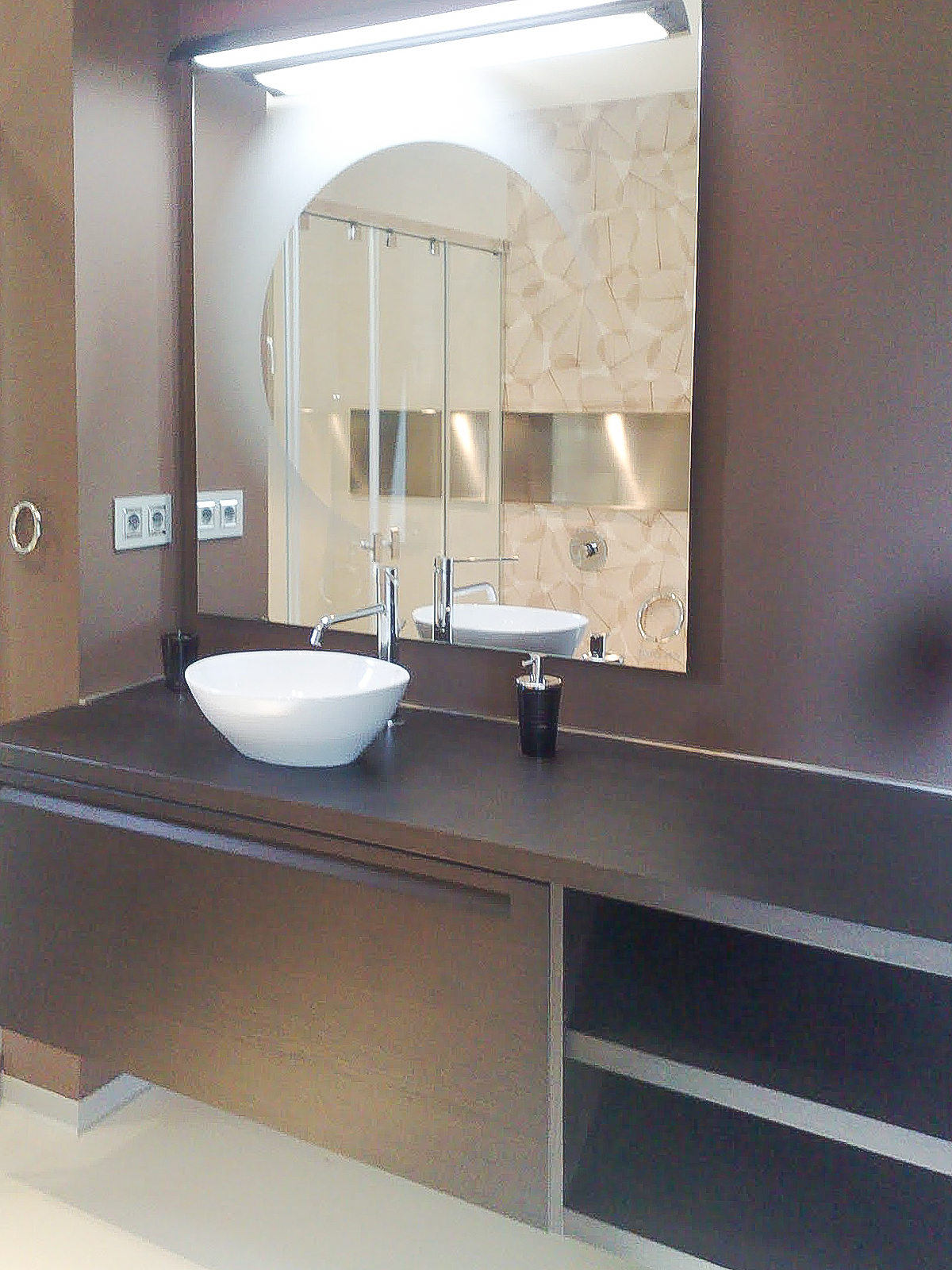 Modern bathroom vanity in dark wood with ceramic sink and square mirror