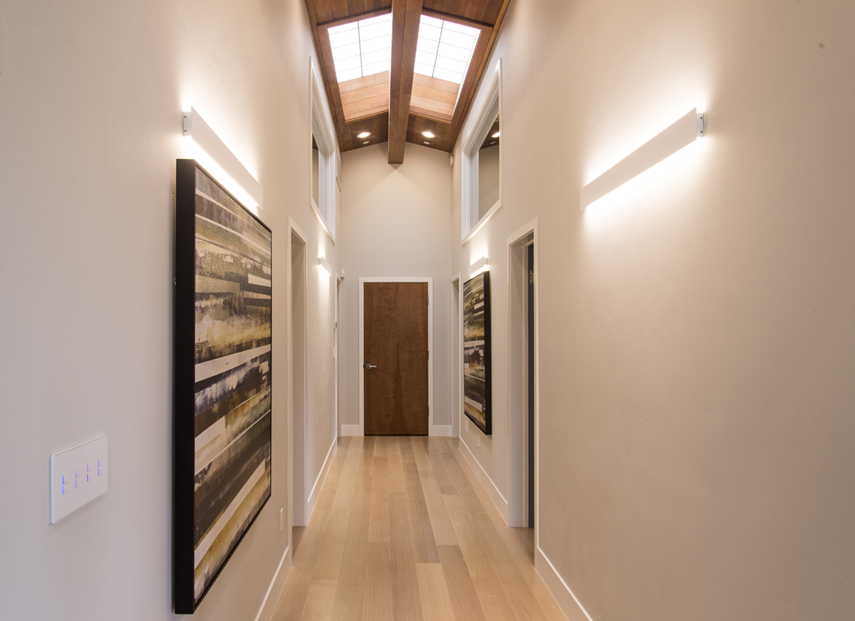 hallway with hardwood floor and sloped wood ceiling