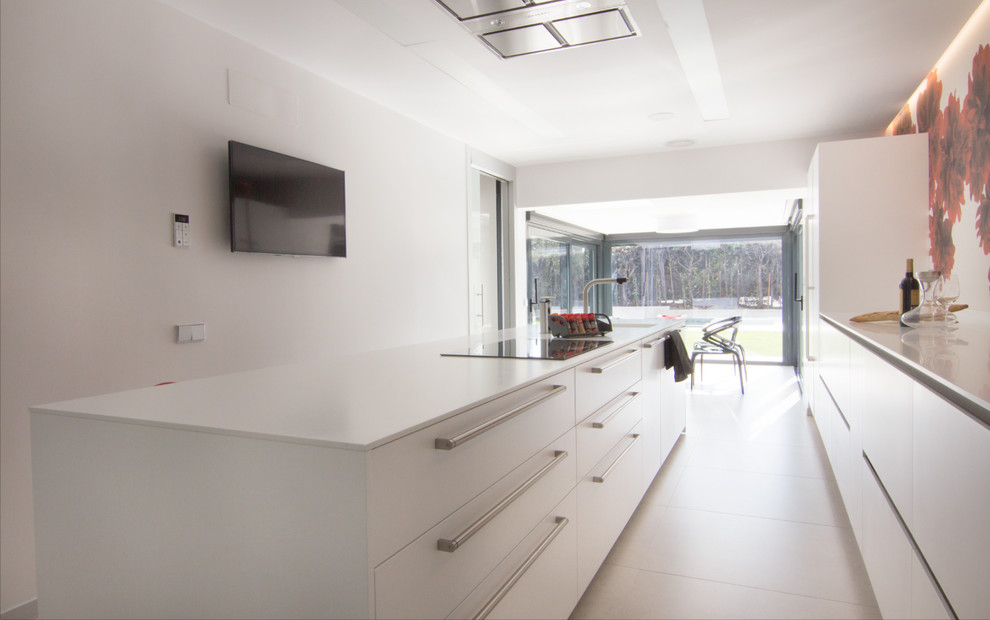 Modern white kitchen with big island and garden view on the back.