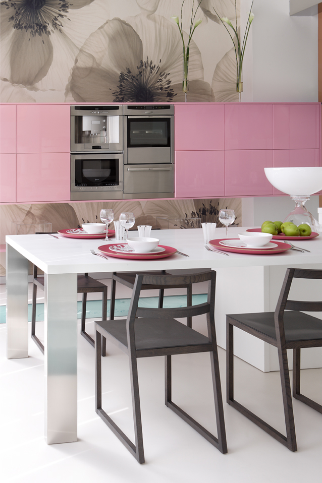 Pink kitchen cabinets and white dining table with dark oak chairs.