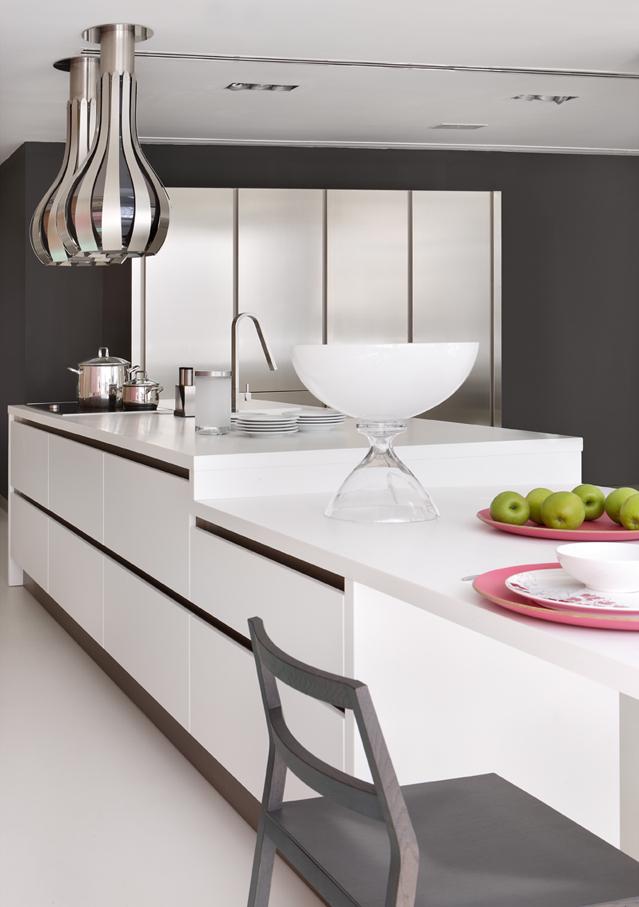 White kitchen island with two decorative hoods and stainless steel cabinets.