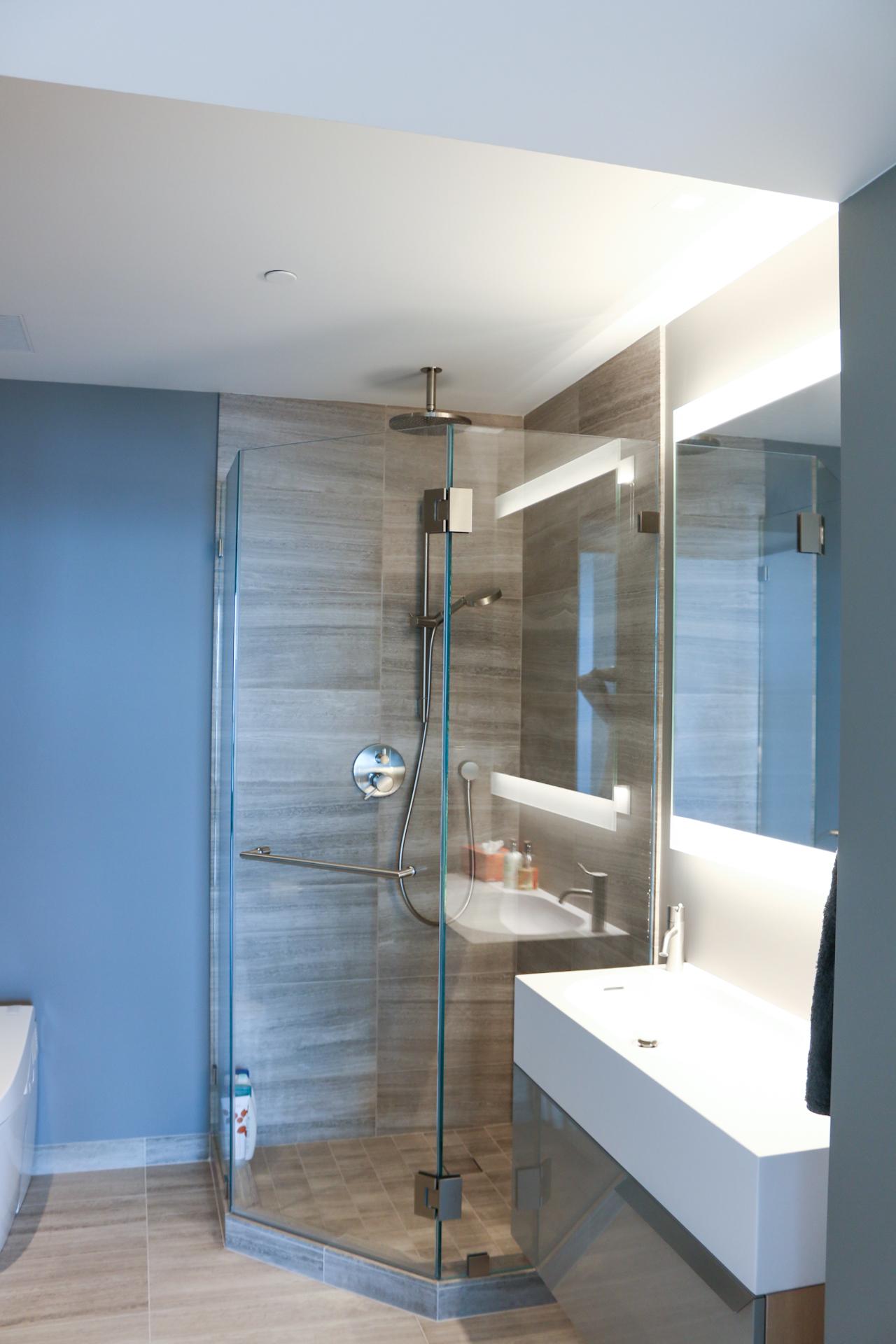 Bathroom with corner shower, limestone tiles and floating vanity