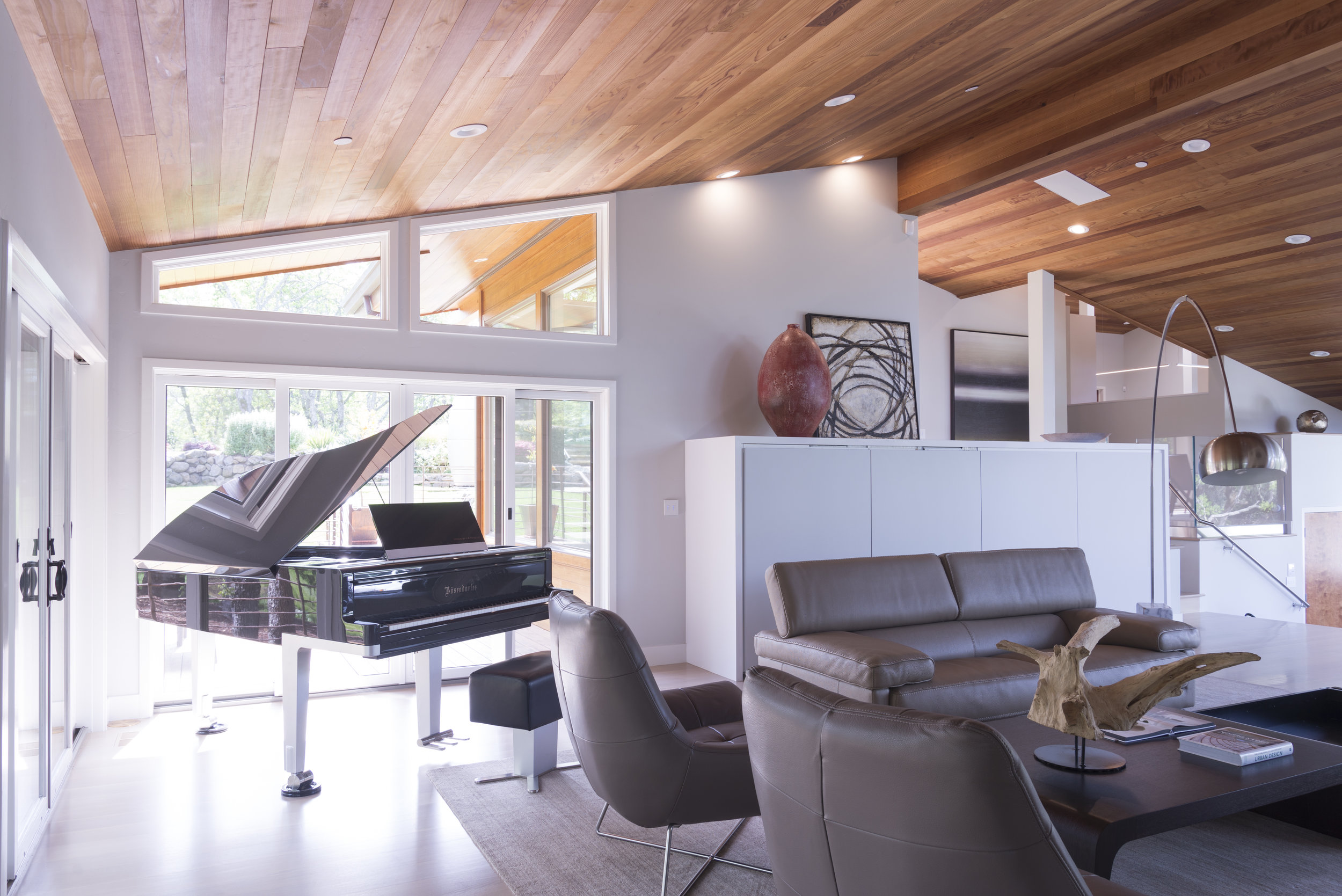 taupe sofa and chairs, a black piano and a grey cabinet