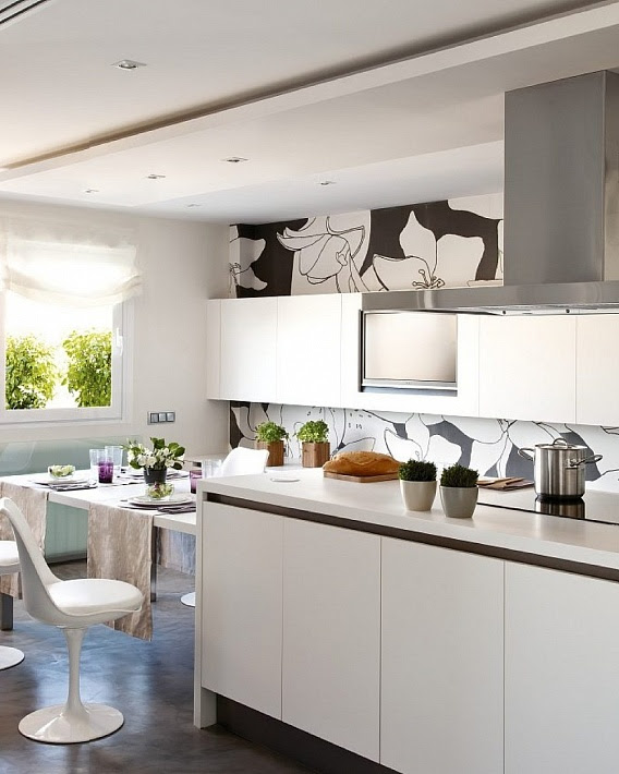 White kitchen with a white and black flowers wallpaper and a swivel chair.