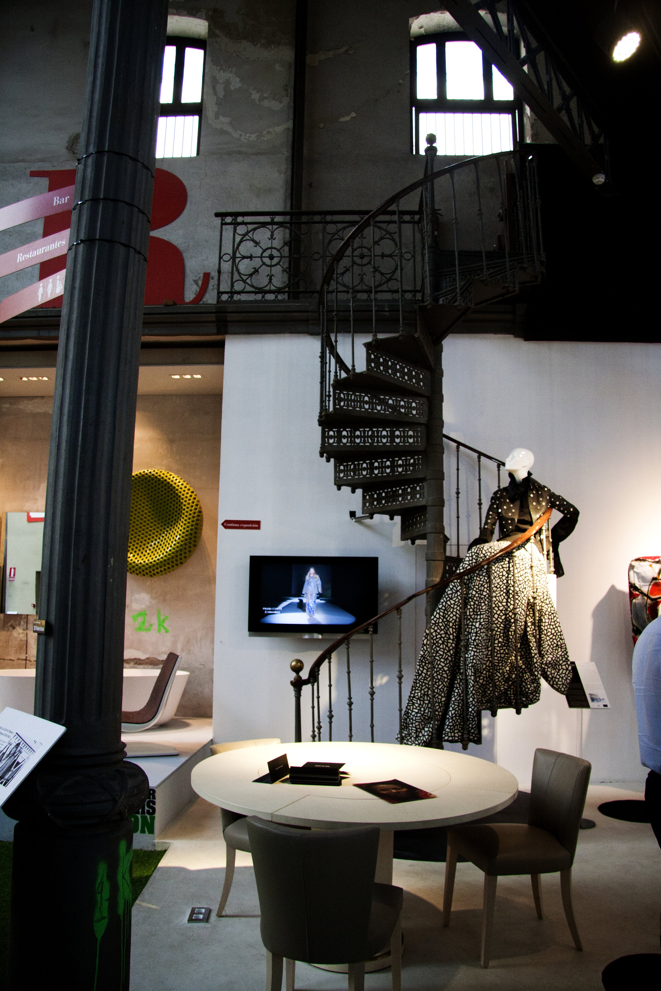 spiral metallic staircase with a woman mannequin and a table with chairs