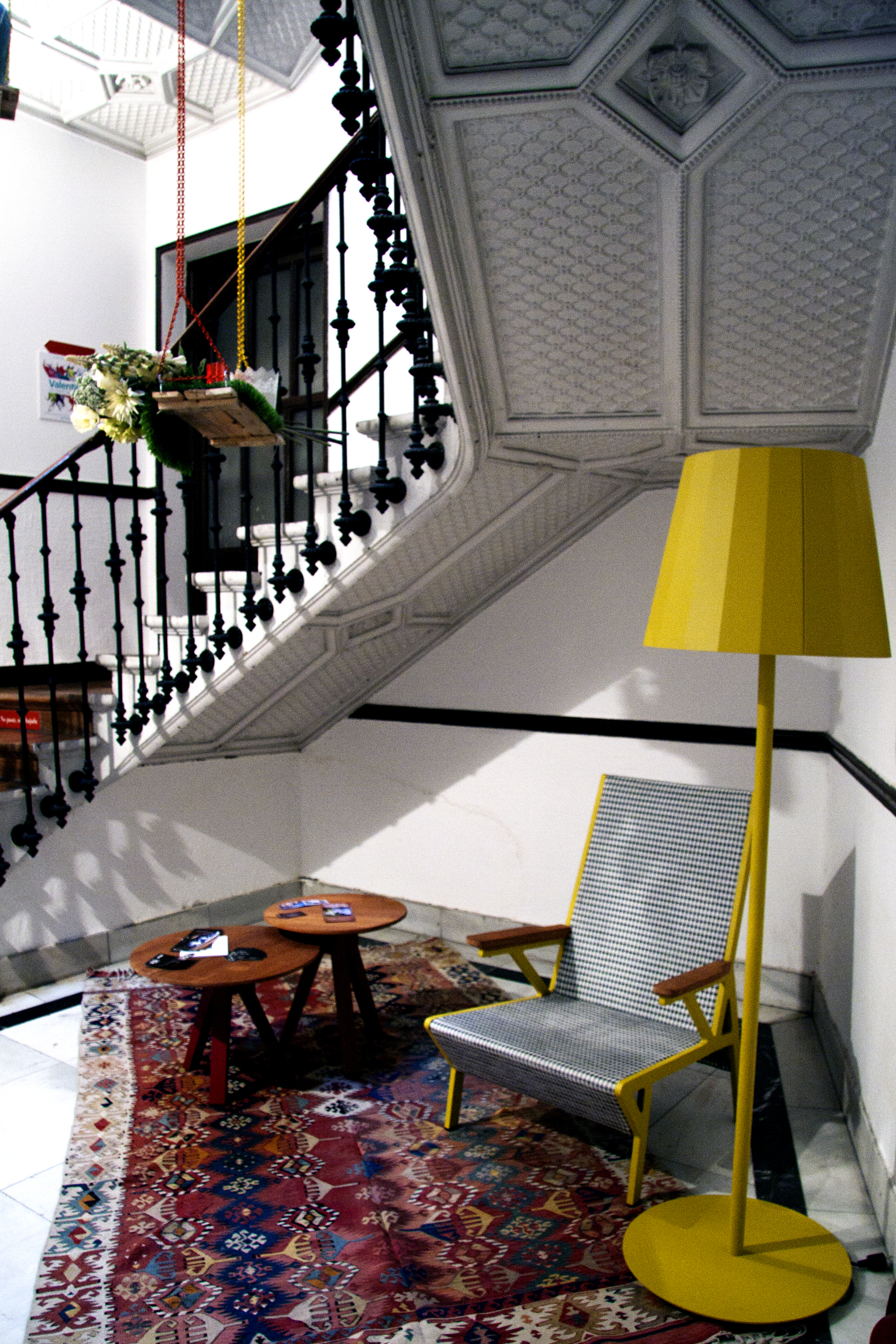 bottom of a staircase with a yellow floor lamp, a chair and a traditional rug