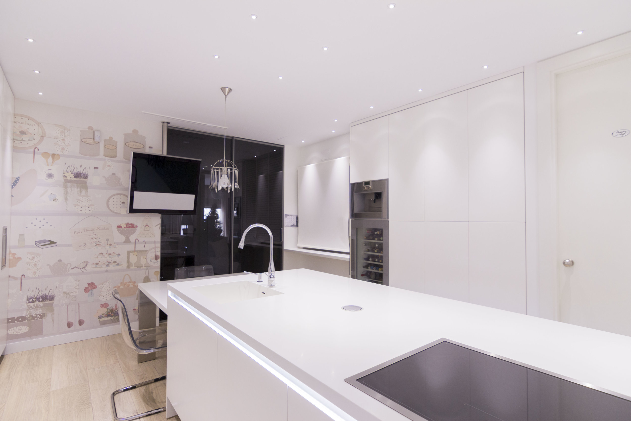 White kitchen and earth tones wallpaper in accent wall.