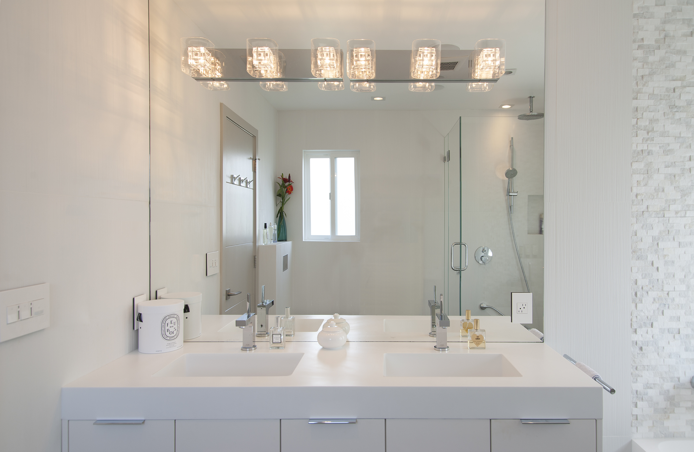 White vanity with two sinks and a mirror with modern wallsconces