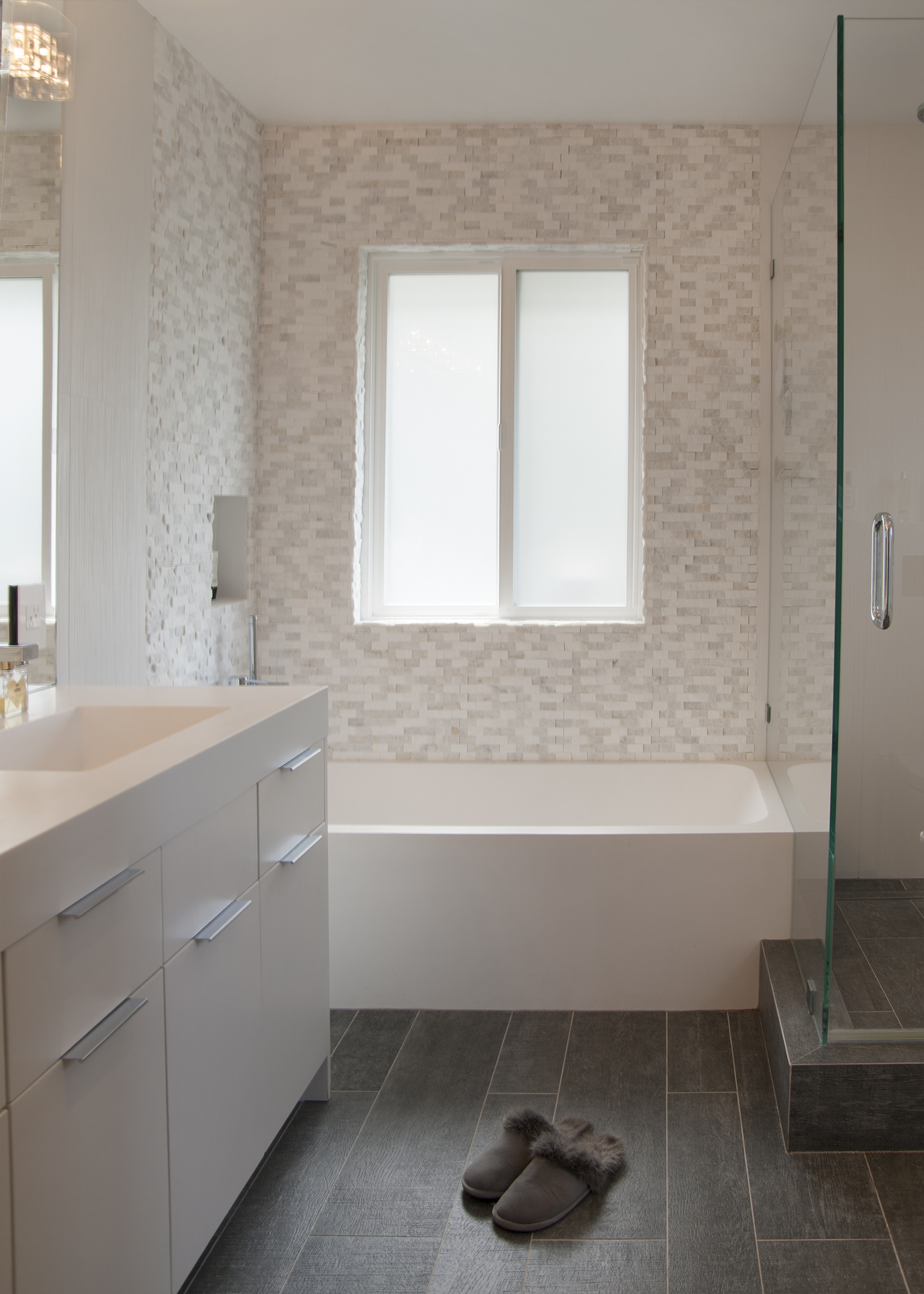 White modern Bathtub and a Porcelanosa marble covered wall.