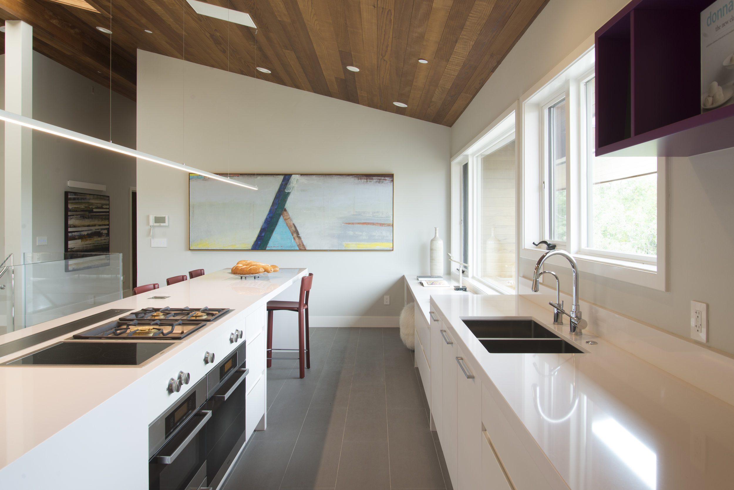 white kitchen with an island, red barstools and a big abstract painting on the wall