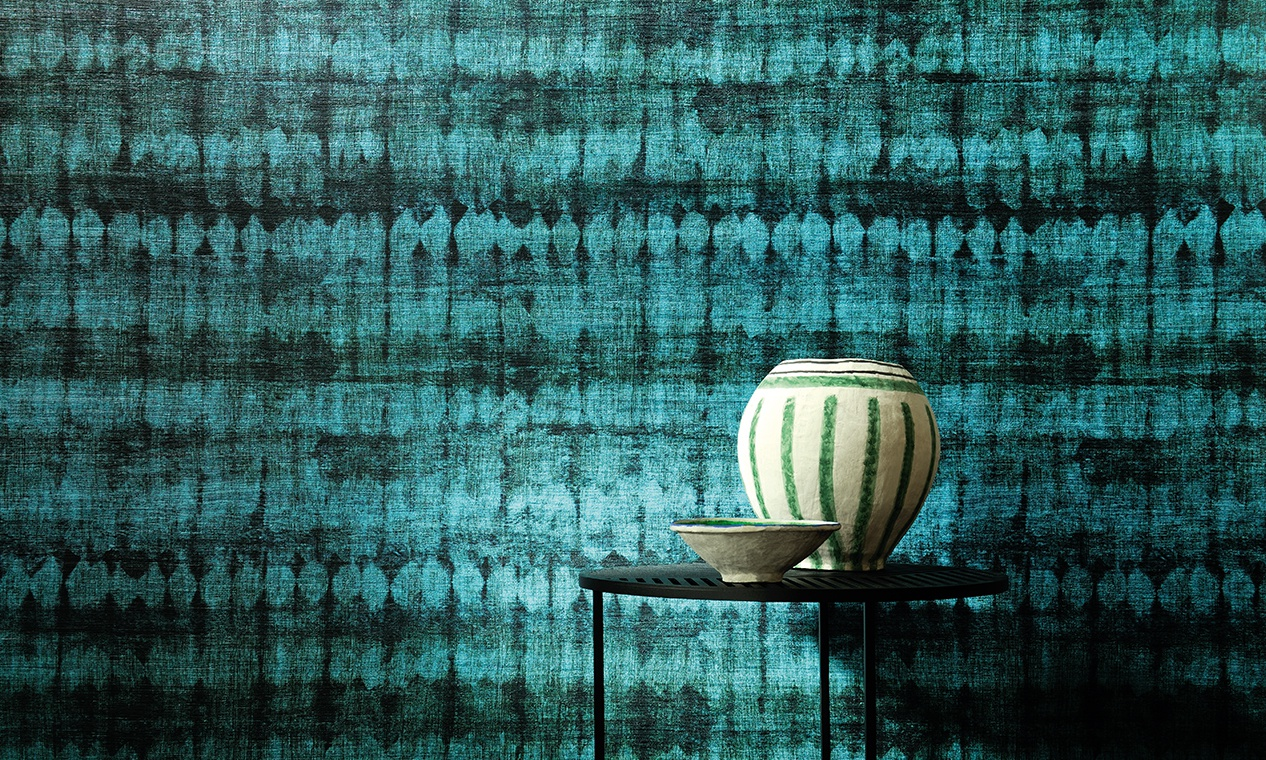 Blue wallpaper and a round table with vases