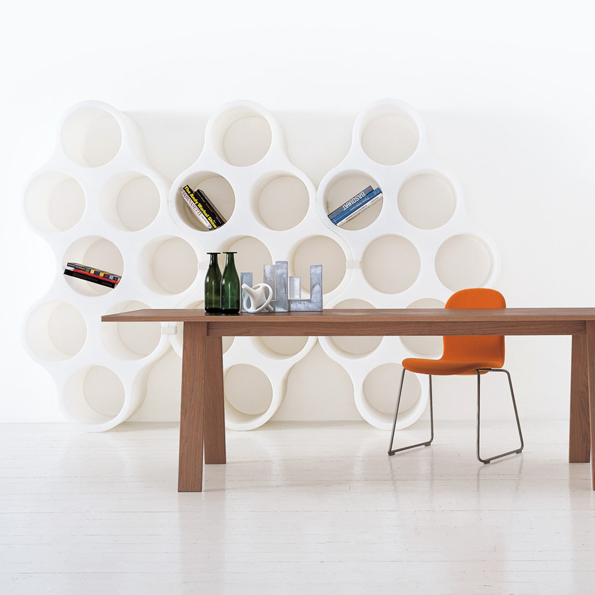 a wood table with an orange chair and a curved bookshelf
