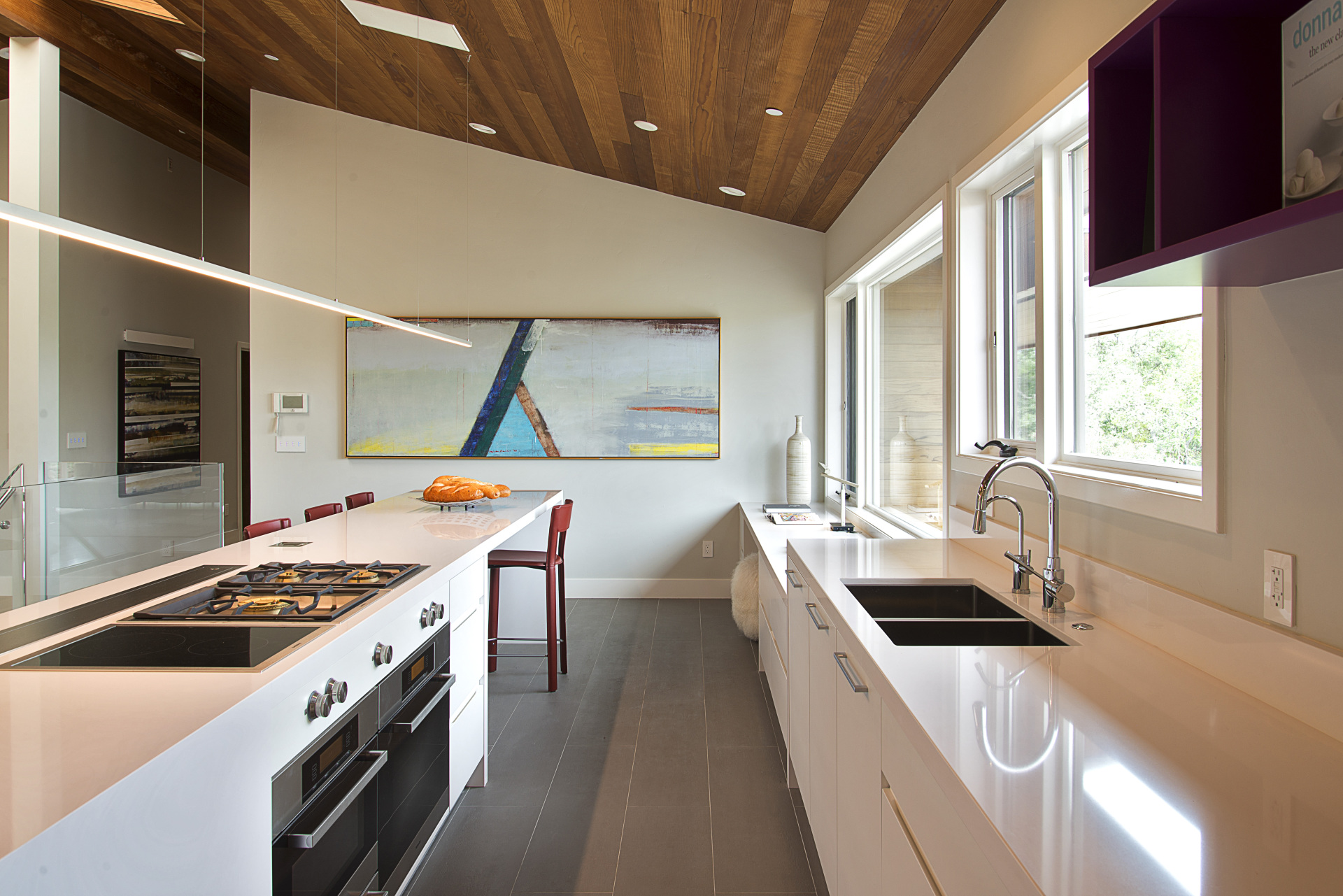 modern white kitchen with sloped wood ceiling