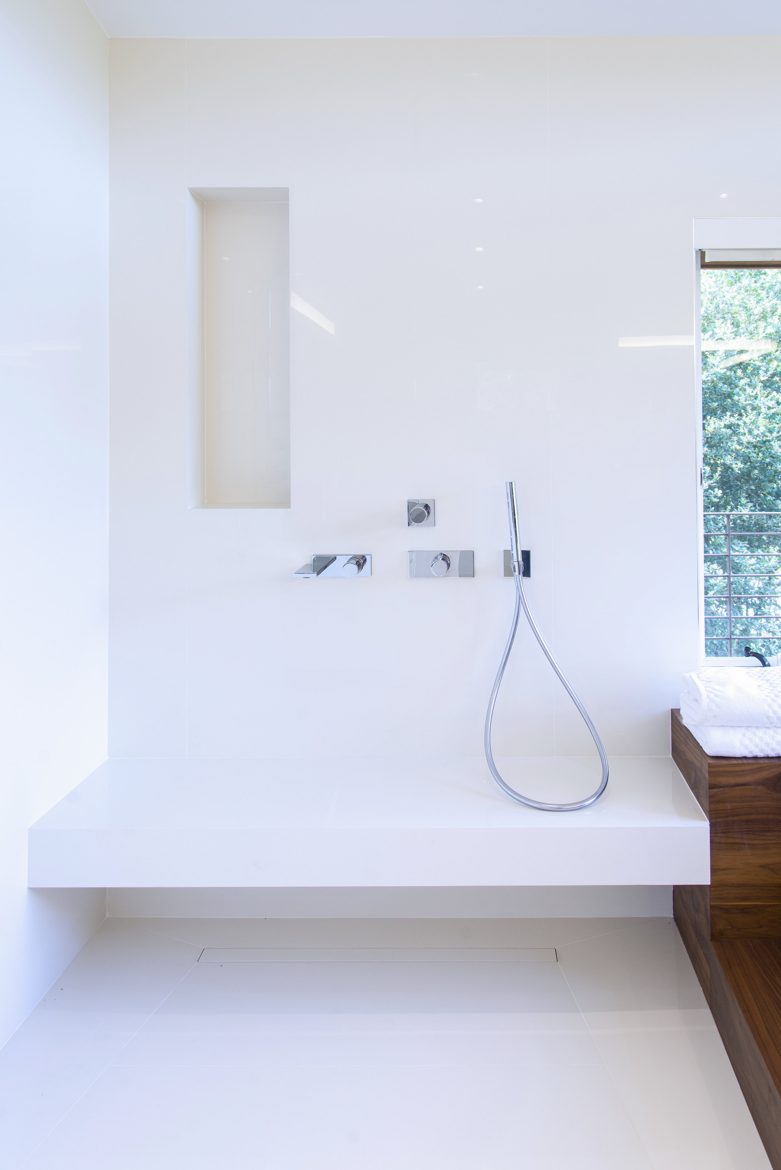 White tile shower very modern with a bench