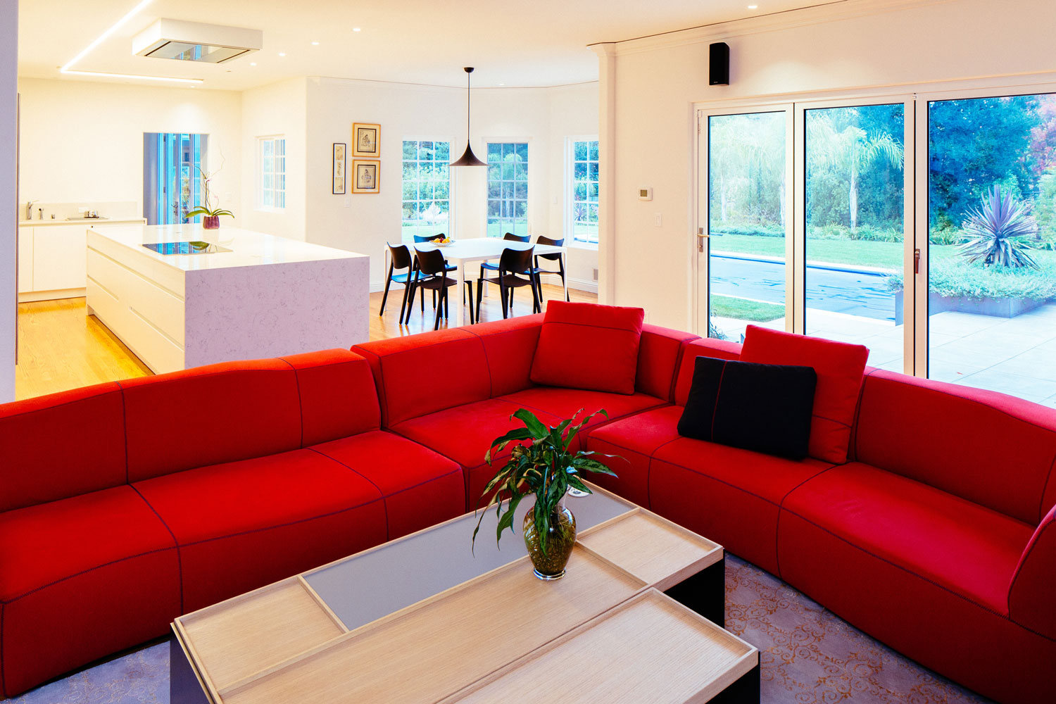 The den features a bright red sectional sofa creating a contrast with the white kitchen.