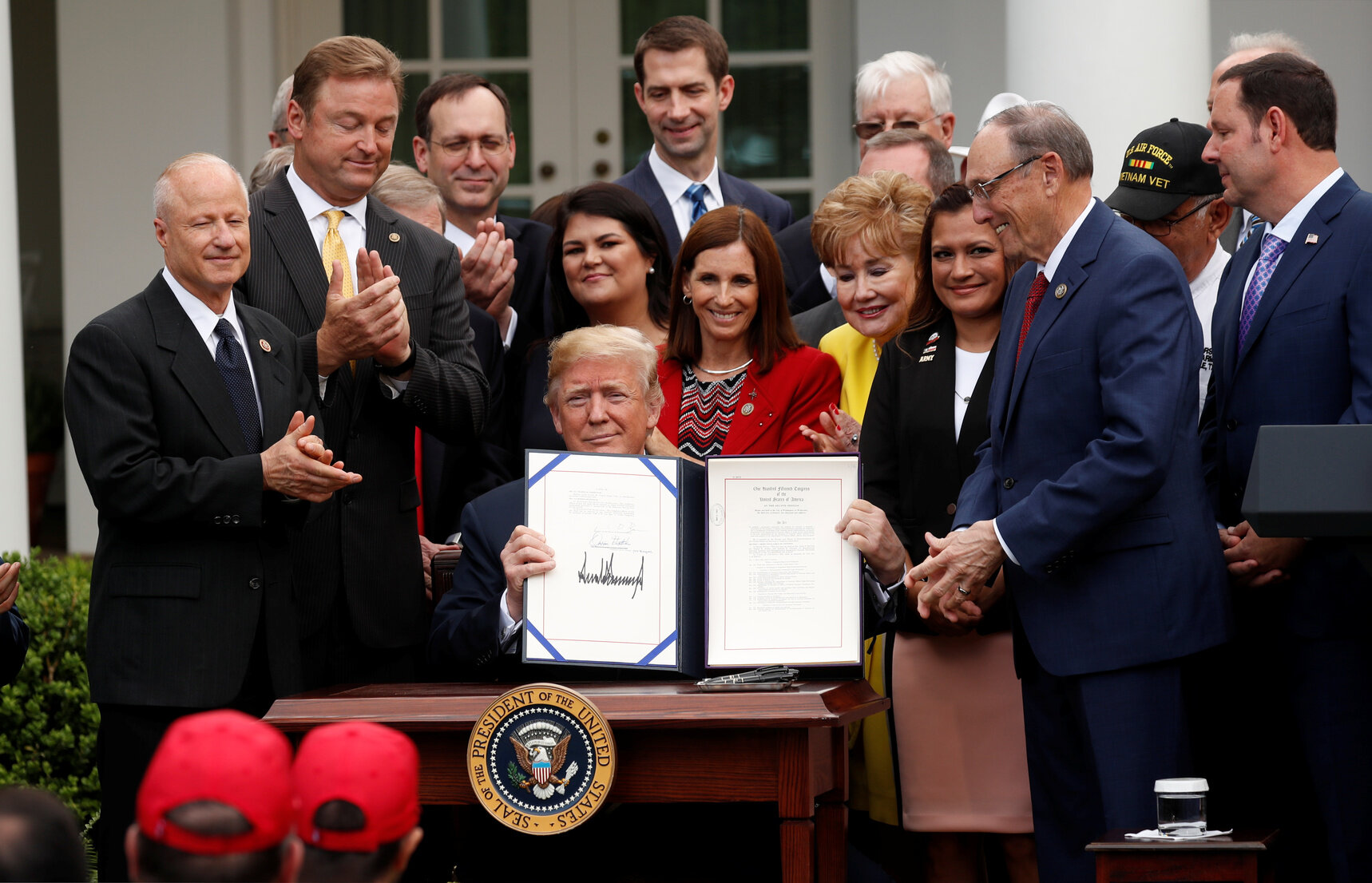 """U.S. President Donald Trump displays the """"VA (Veterans Affairs) Mission Act of 2018"""" after signing it in the Rose Garden of the White House in Washington, U.S., June 6, 2018. [REUTERS/Kevin Lamarque]"""