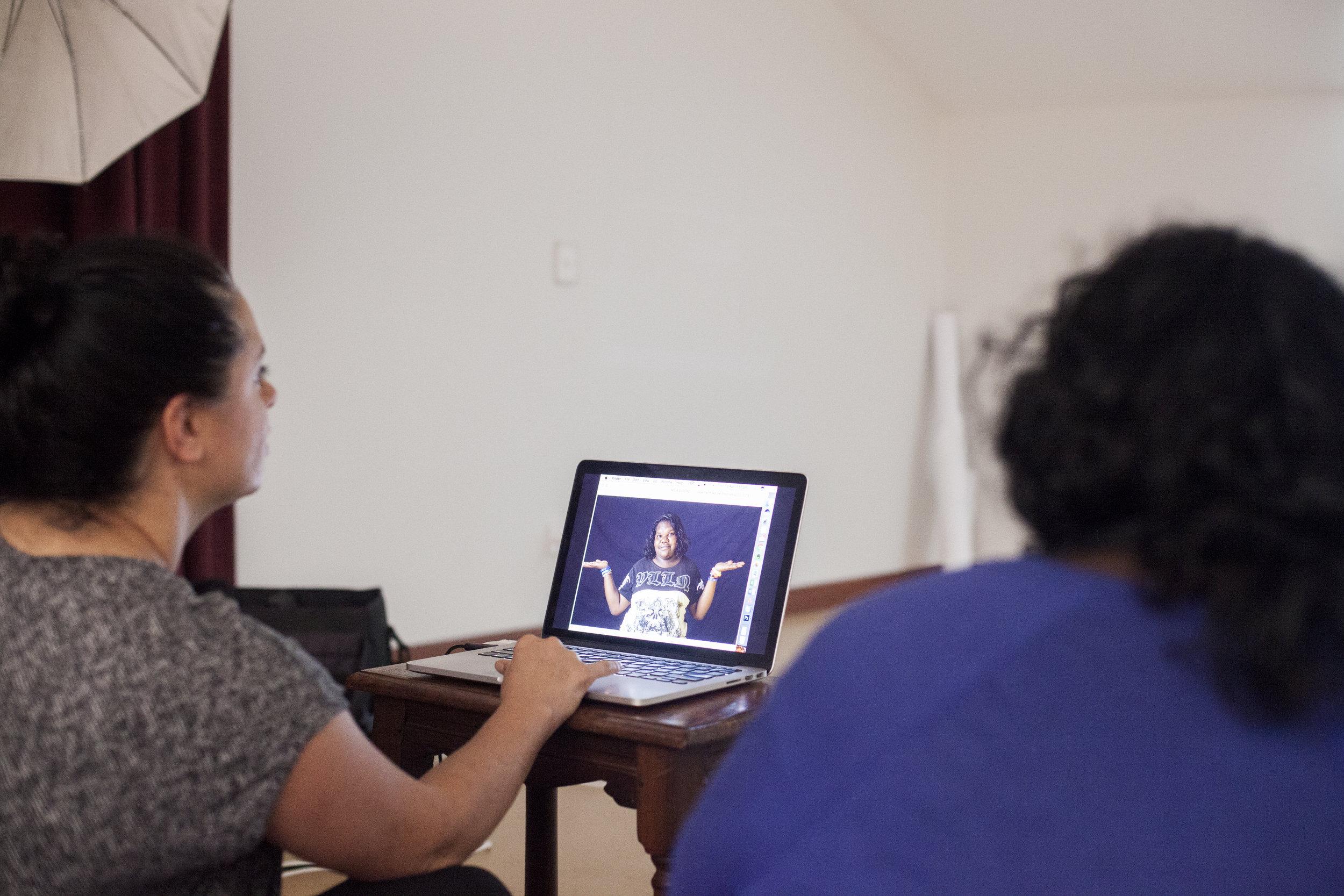 Maria Fredericks and Christine Tomas reviewing and editing studio portraits.