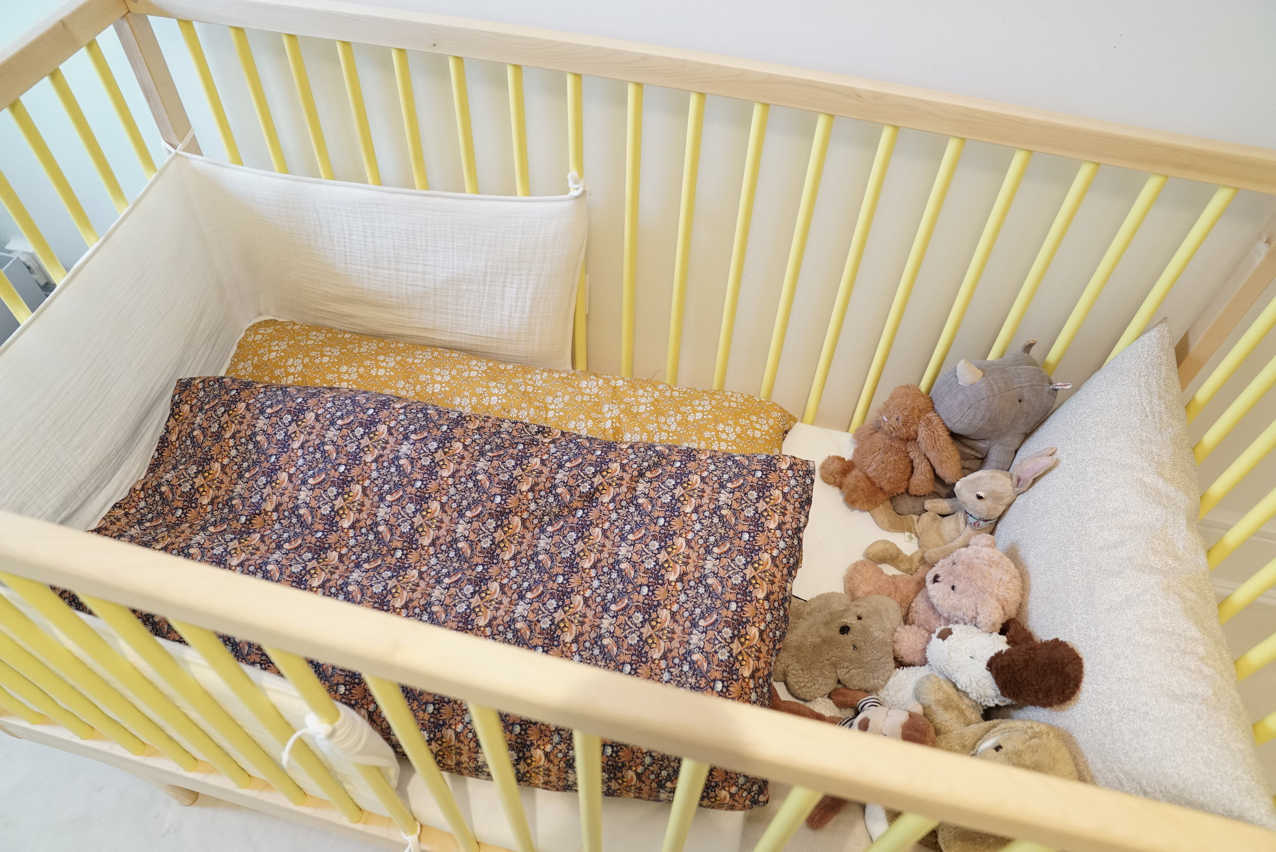 The  Caravan Crib  in yellow, and  bed bumper  in the color 'Milk'. Liberty duvet covers from  Liberty by Lyngholm .