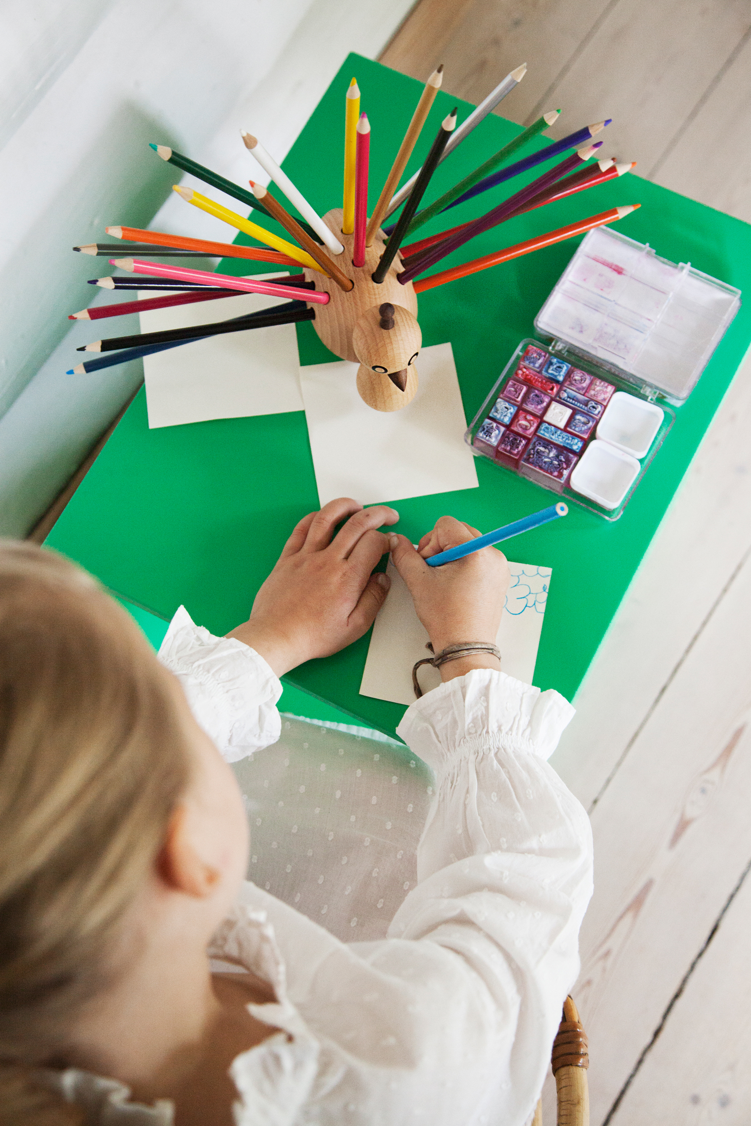 Carla, who's wearing the  Martha dress , is drawing with the colour pencils from the  Peacock Pencilholder .