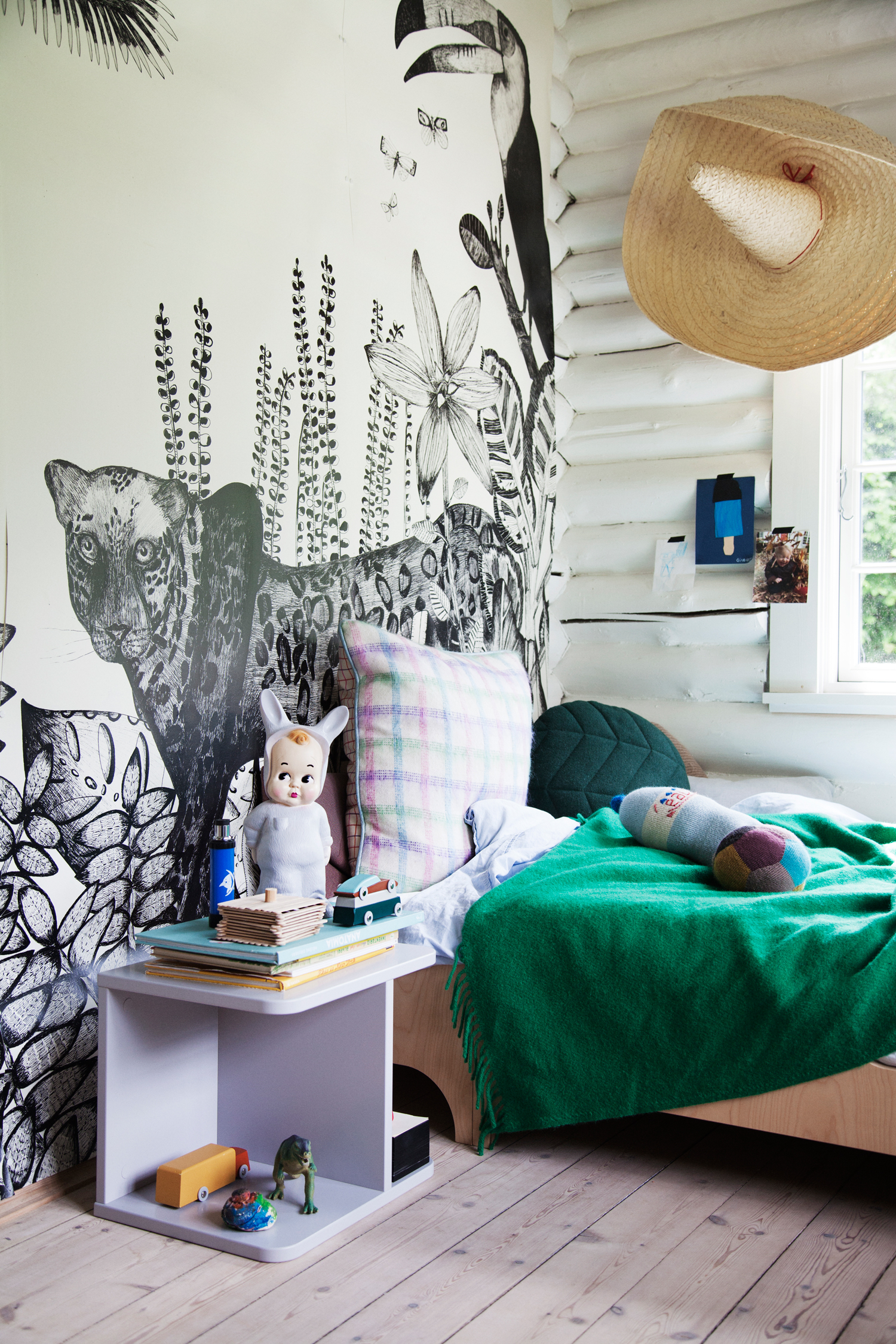 'The Wild'  wallpaper makes for a great background for the  A Teen Bed  in Gilbert's room. Next to the bed is the  3-in-1 Chair  used as a table. On the table: A  Baby Lapin Nightlight  and  Duotone Cars , while a  Water Bottle pillow  lies on the bed.