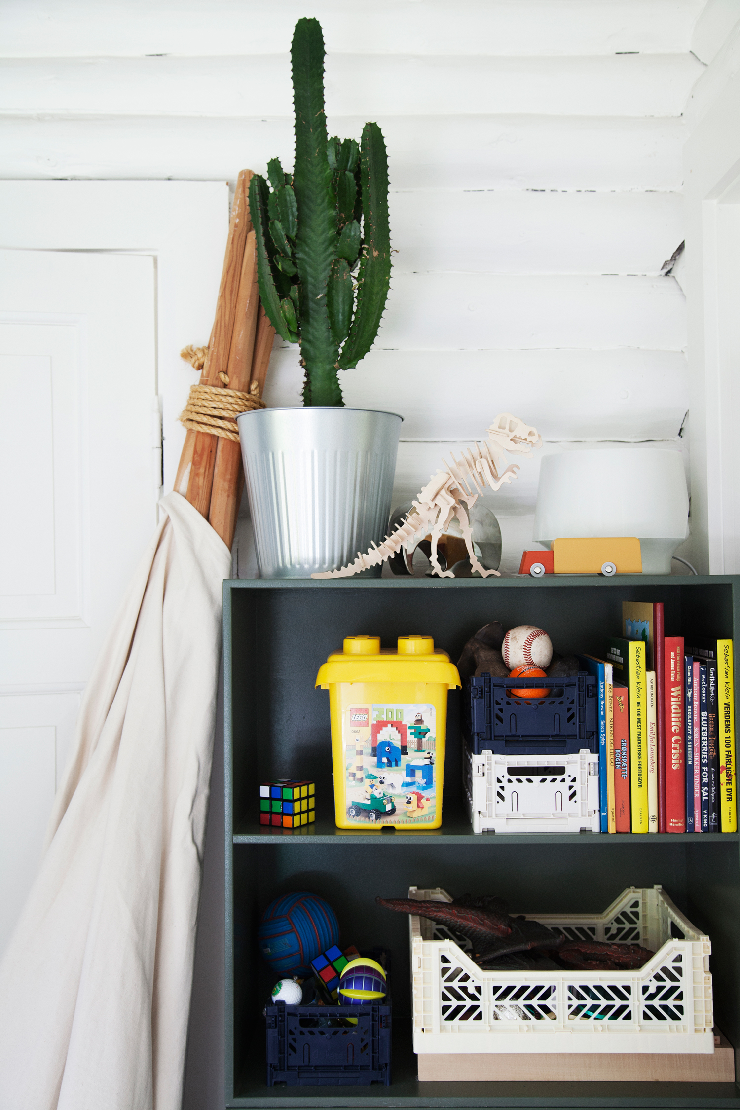 Next to a handmade tipi stands a  Dinosaur Wooden Puzzle  and a  Duotone Car .  Mini and midi storage boxes  are used to store toys throughout both children's rooms.