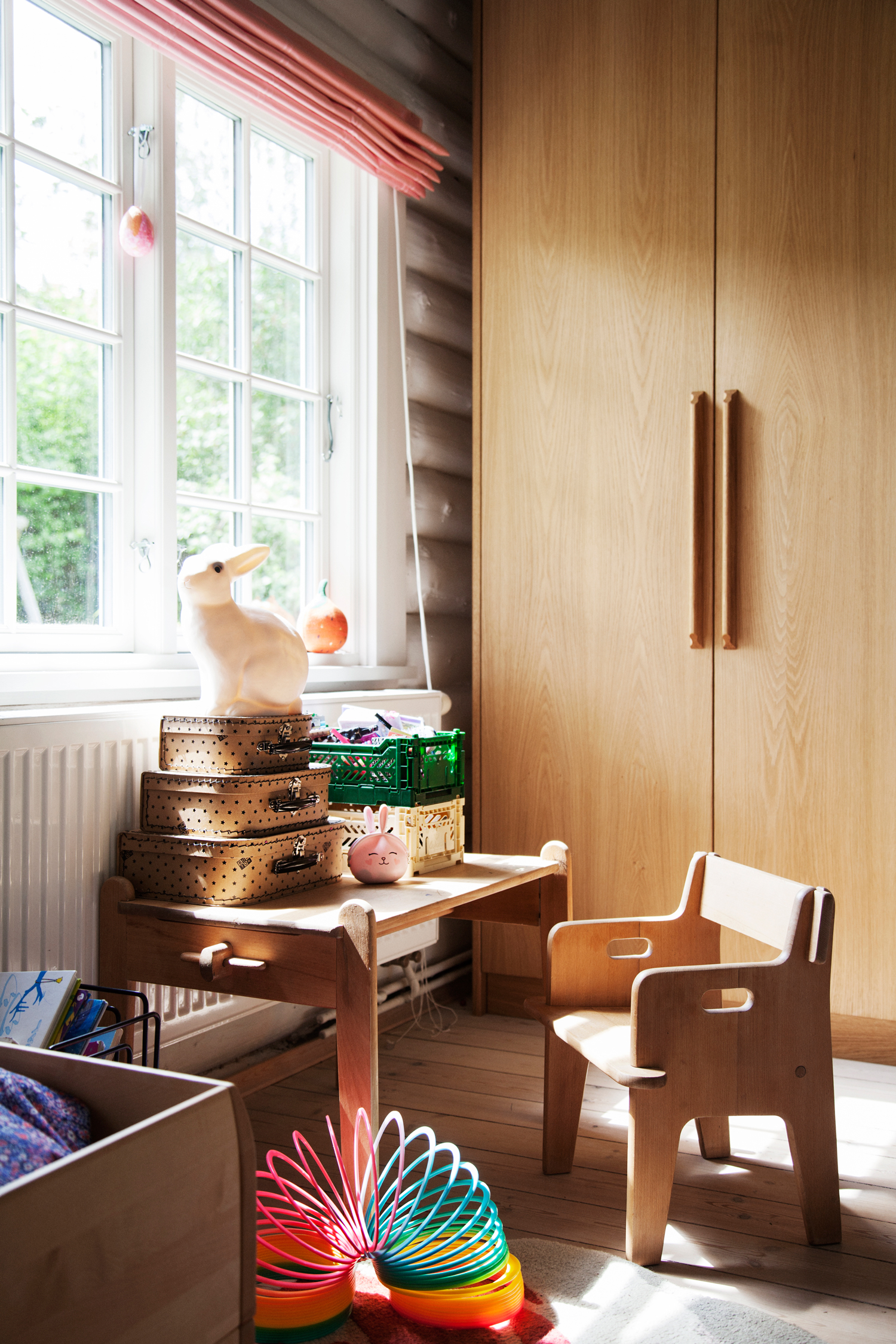 A corner in Carla's room, showing a glimpse of the handmade  Echo Bed , the  Bunny Lamp  and  foldable boxes  on the table.
