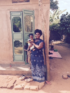 Proud ITW mother stands outside clinic with her young healthy baby.