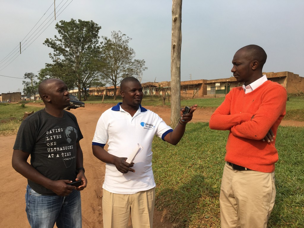 Picho and Collins talk with the leader of the Village Health Team in Kasambya.
