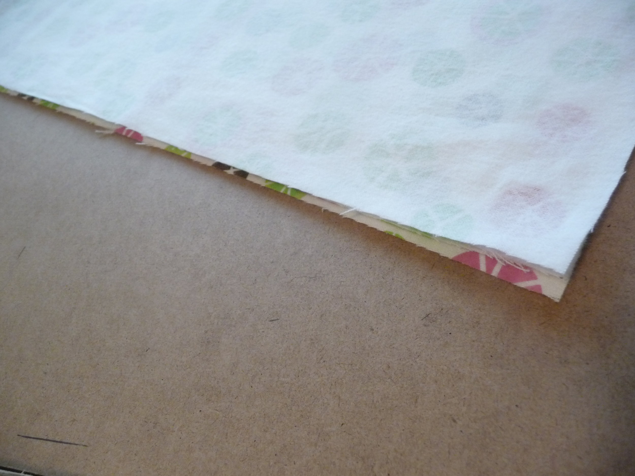 #4 - After folding the fabric over twice smooth it out so the cut edges are as straight and lined up with the fabric underneath. If you look at the picture above you will see because of how the fabric was originally cut they do  not all line up straight. With a cut along this edge you can straighten it right up, ready for the cutting of diapers.