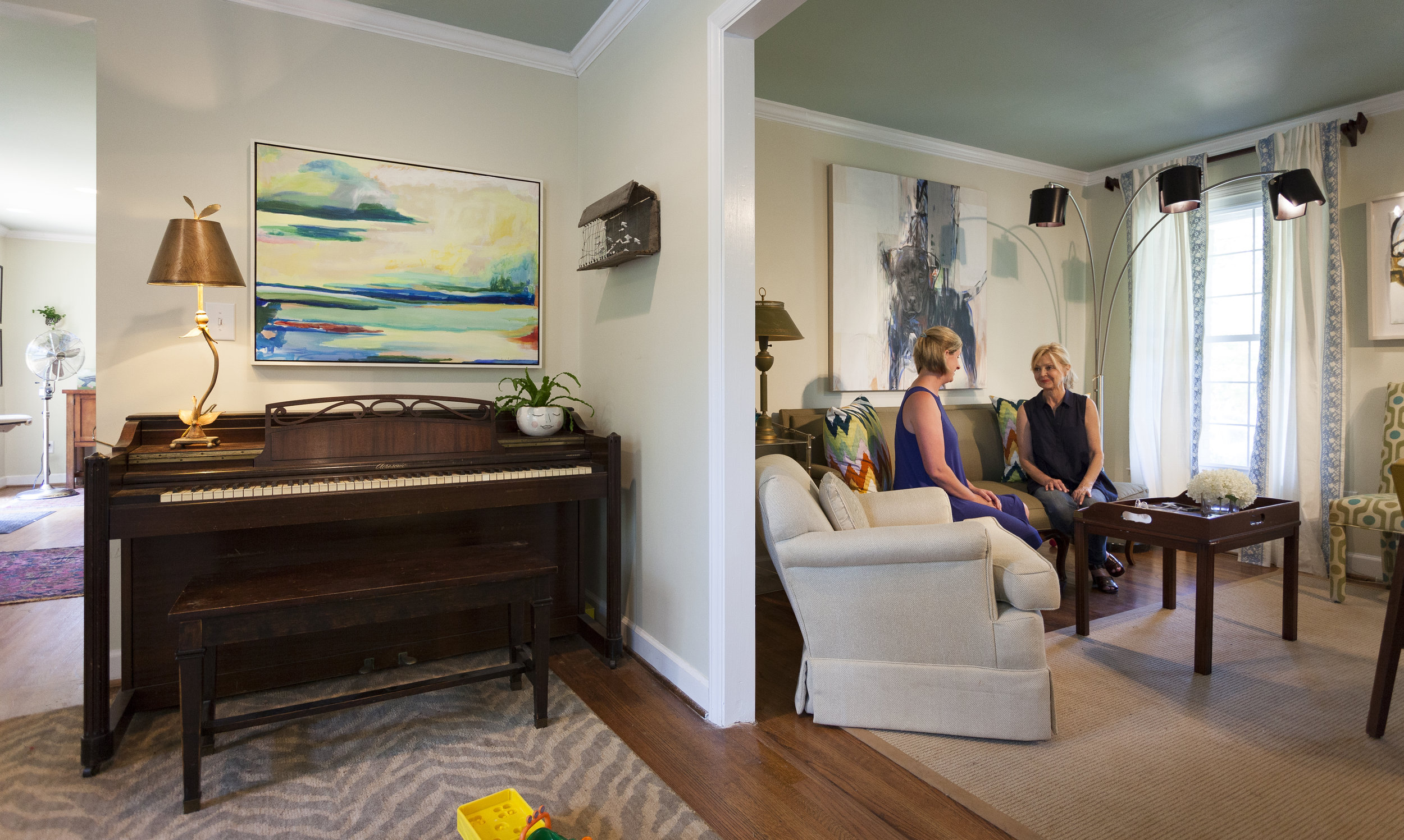 a  Kiah Bellows  landscape hangs above the piano and  Heather LaHaise's  pup is over the couch.