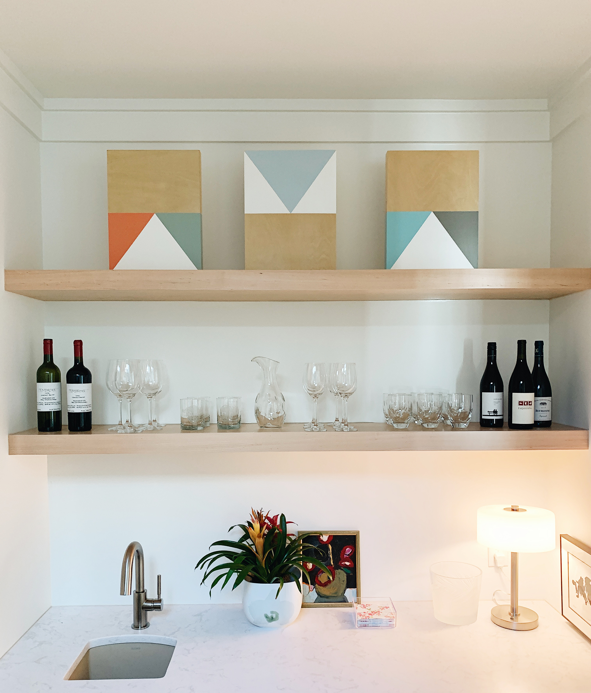 Pieces by Jeffrey Leder create perfect harmony above this wine bar. Below, a small work by Katie Walker brings some rich color to the space.
