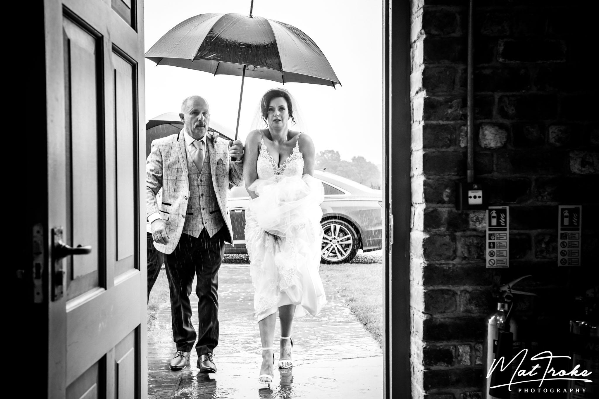hazel-gap-barn-wedding-photography-raining-umbrella