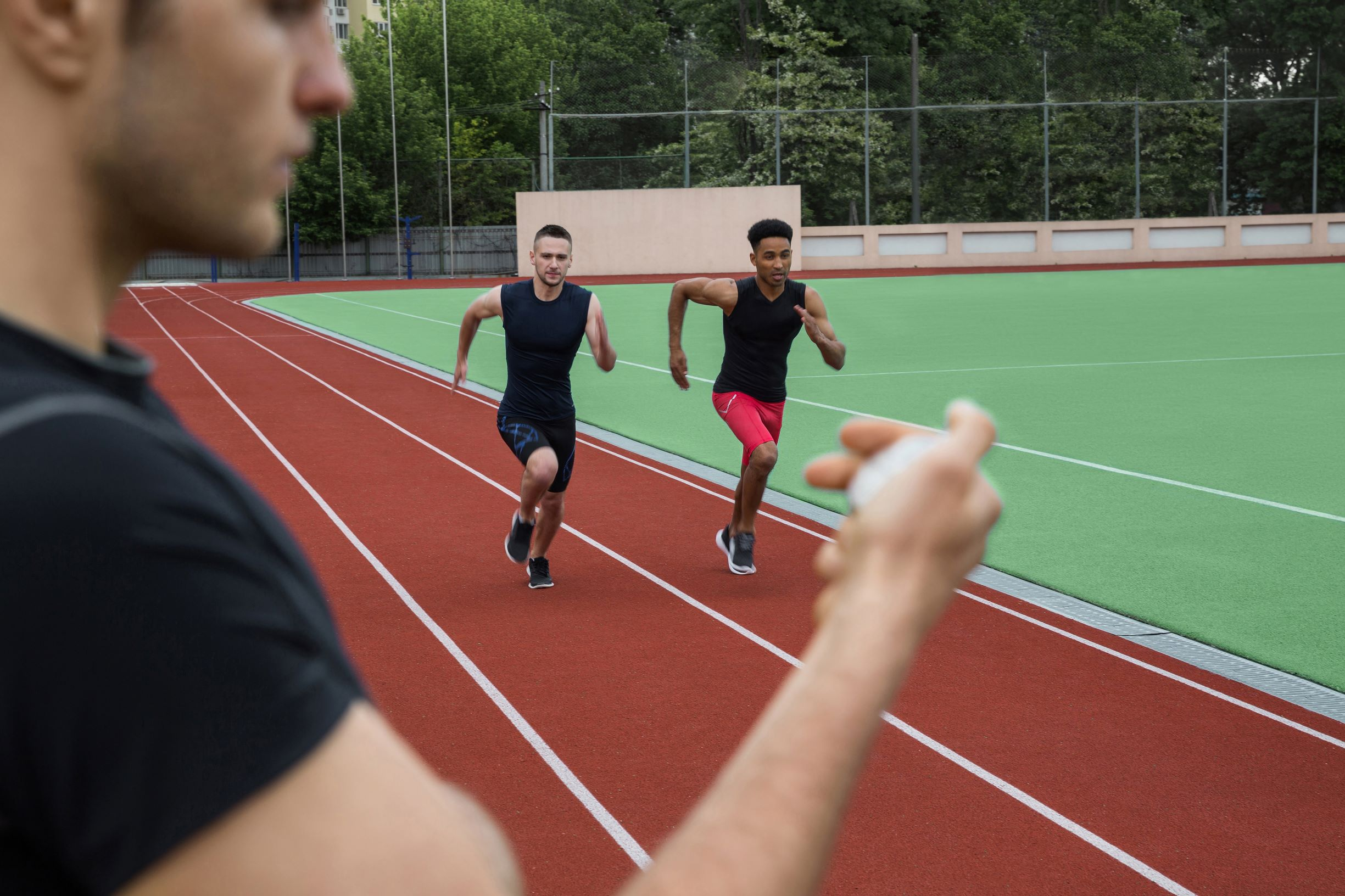 storyblocks-image-of-young-multiethnic-athlete-men-run-on-running-track-outdoors-historic-stop-watch-time-measurement_HCxUy7npc-.jpg