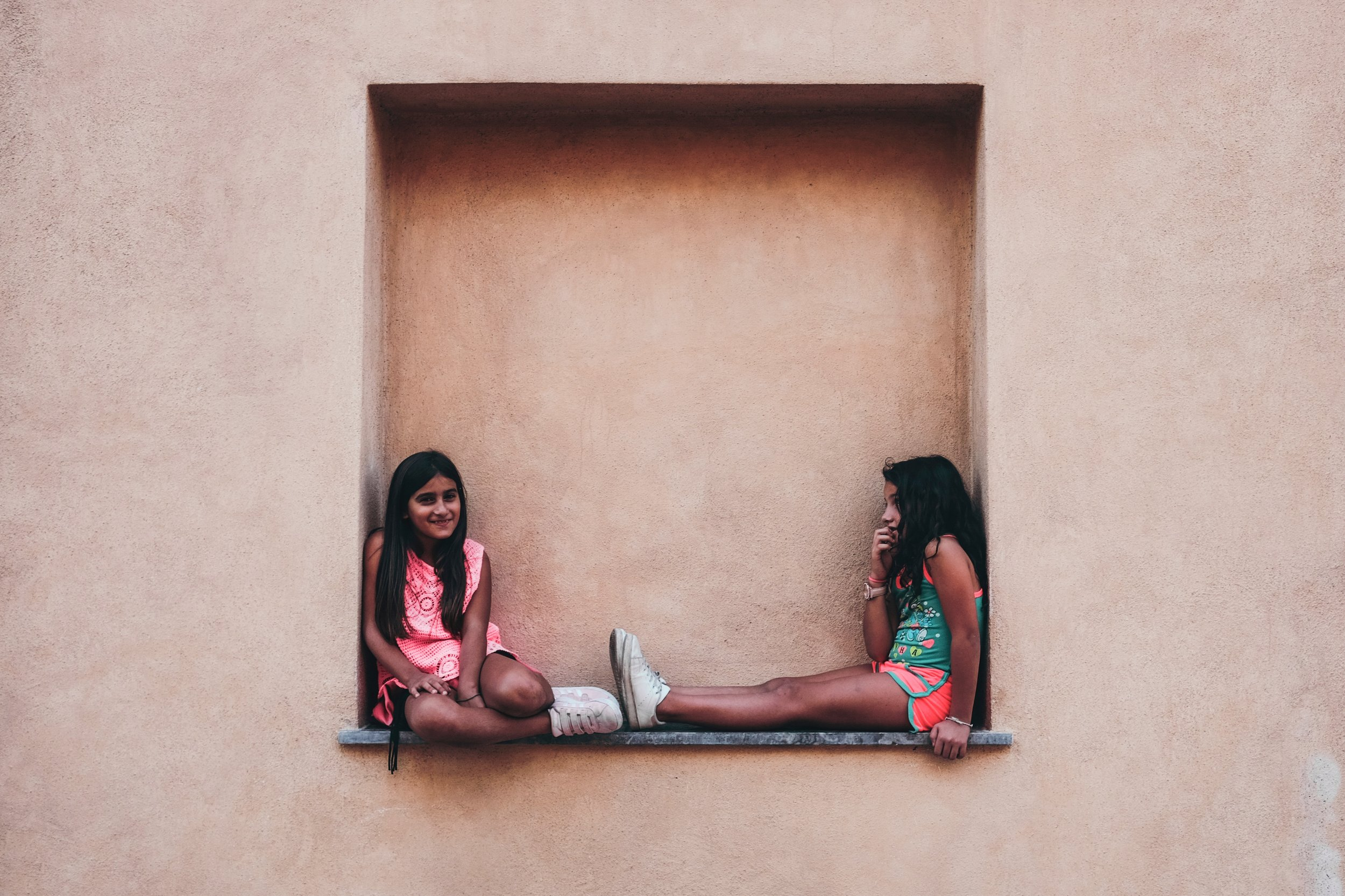 girls sitting on wall