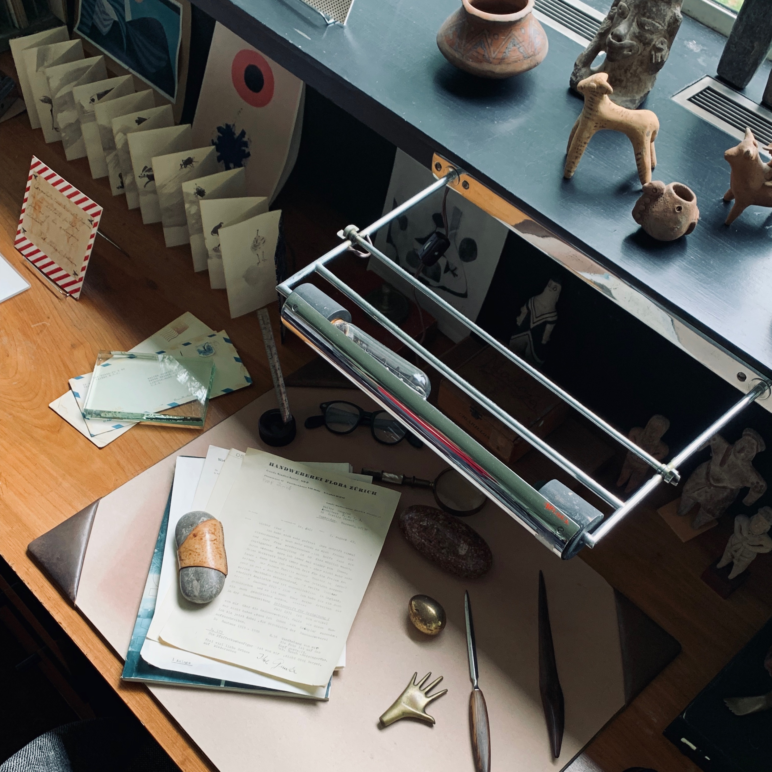 The desk of Walter Gropius, features lamps by Marianne Brandt and pre-Colombian artifacts from Diego Rivera and Frieda Kahlo.