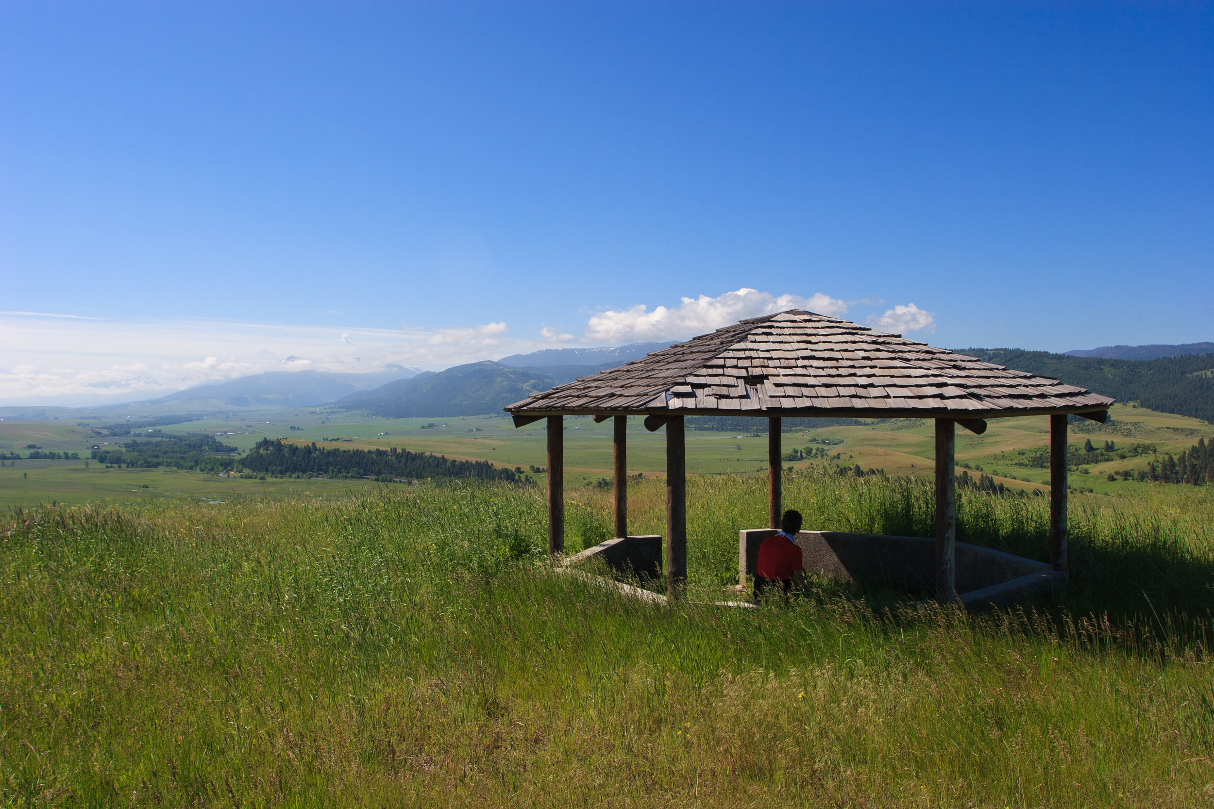 A visitor rests in the gazebo overlooking the Wallowa Valley