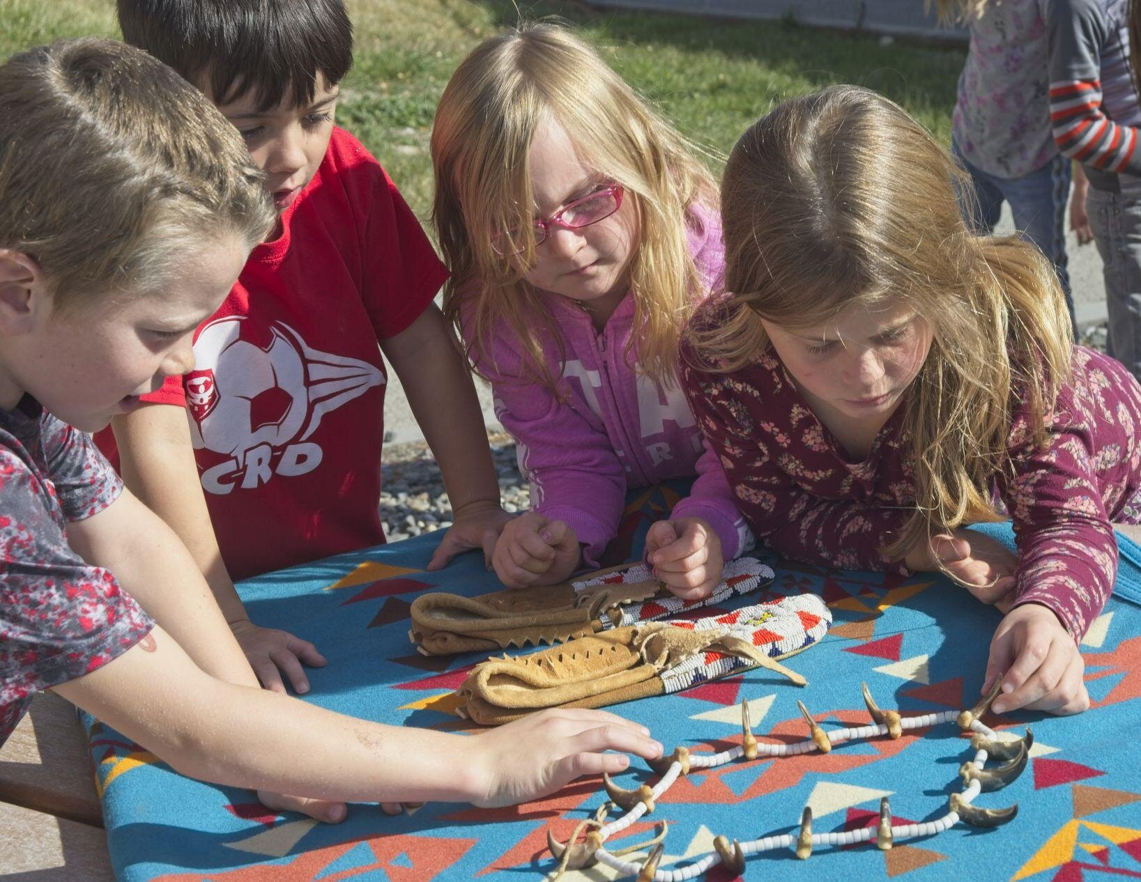 First graders in Mrs. Hook's Enterprise Elementary School class examine a real bear claw necklace and beaded moccasins as part of understanding the close relationship between the Nez Perce and the natural world. The event was part of the school's celebration of Indigenous Peoples Day.
