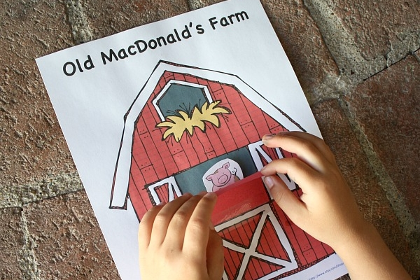 Fun and free kids farm activities, picture of a child playing with a peekaboo barn.