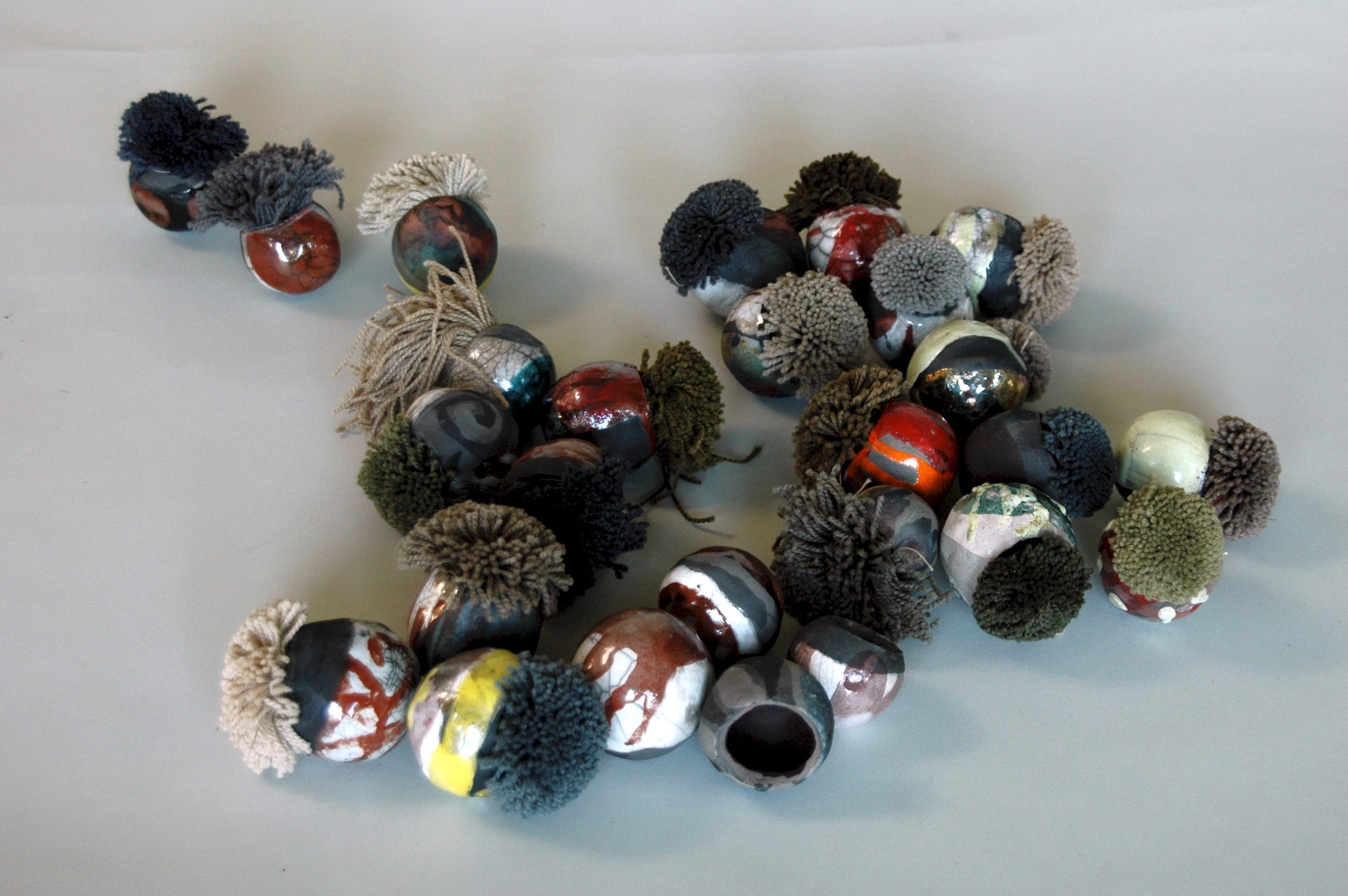 """Symbiosis: echinoderms, sea urchins, were my inspiration. Acclimating to new culture is like being at home with the strange and the discomforting and still learning to find ease with them.  2""""h x 24""""w x 24""""d  Clay, Carpet samples  2009"""