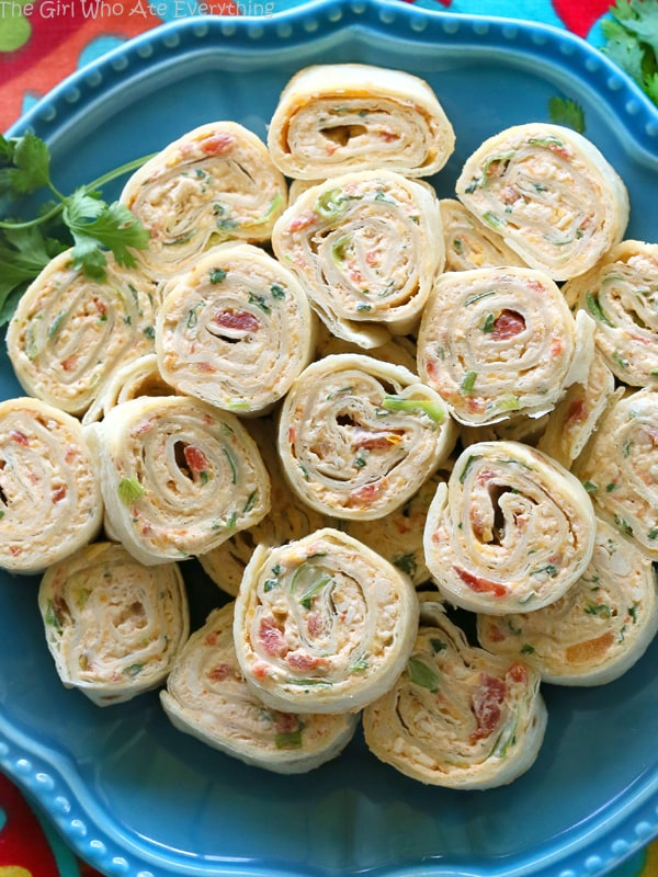 Chicken Enchilads Roll-Ups - INGREDIENTS2 (8-oz) packages cream cheese, softened1 1/2 cups shredded Mexican cheese2 tablespoons Old El Paso taco seasoning2 cups shredded chicken (rotisserie chicken works well)1 (10-oz) can diced tomatoes with green chilies, well drained1 teaspoon minced garlic4 green onions sliced1/2 cup chopped cilantro8 burrito sized tortillasINSTRUCTIONSIn a large bowl, combine all of the ingredients (except tortillas) until well blended.Spread about ½ cup of the mixture over the entire surface of a tortilla. Roll up tightly. Repeat with remaining tortillas.Refrigerate until firm, at least 30 minutes. Also, if you chill longer they will be easier to cut.Slice into 1/2 inch slices with a serrated knife to prevent crushing and serve.