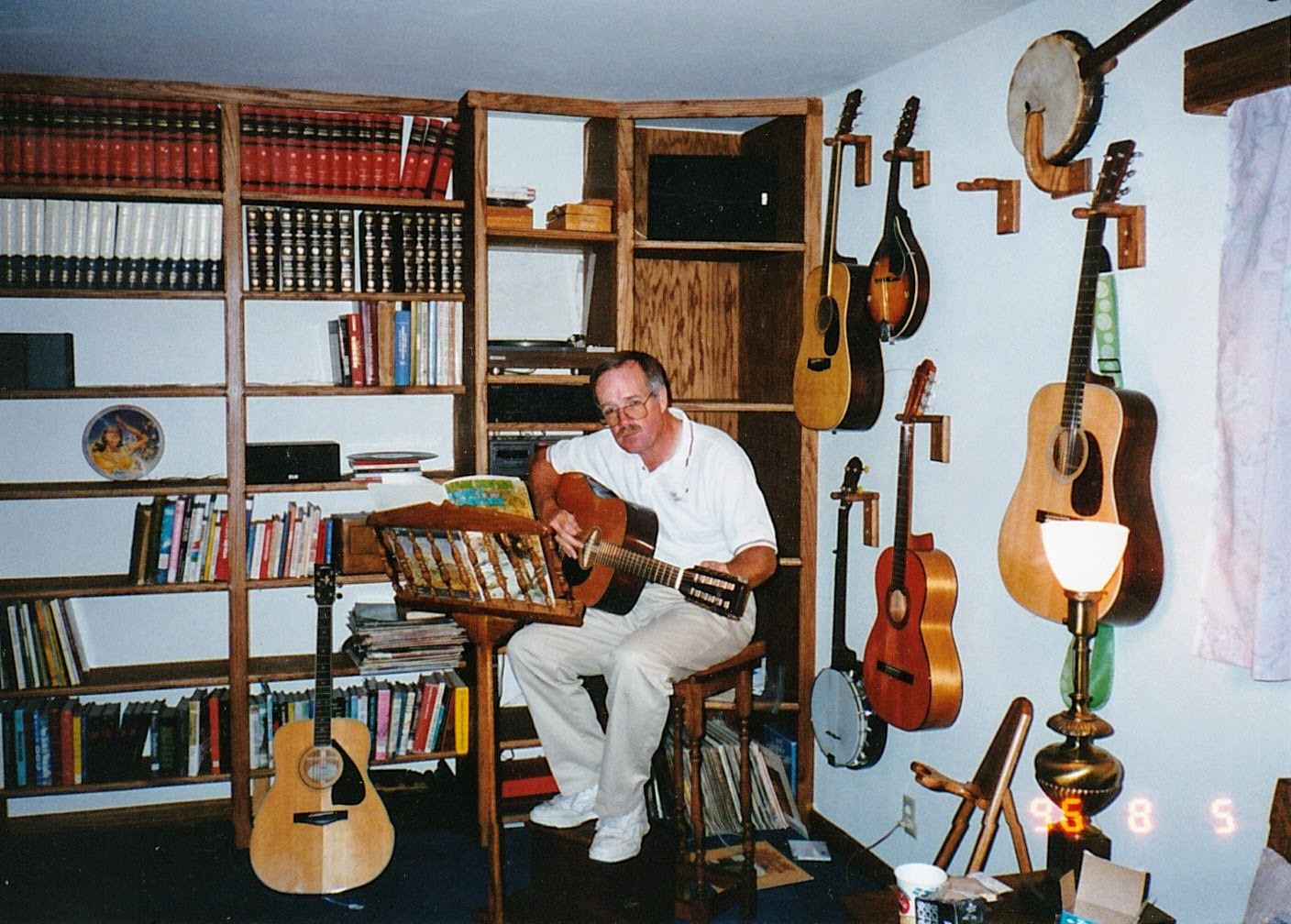 Pretty much everything made of wood in this photo was made by Dad: Music stand, stool, bookshelves, guitar hangers, and even some of the guitars!