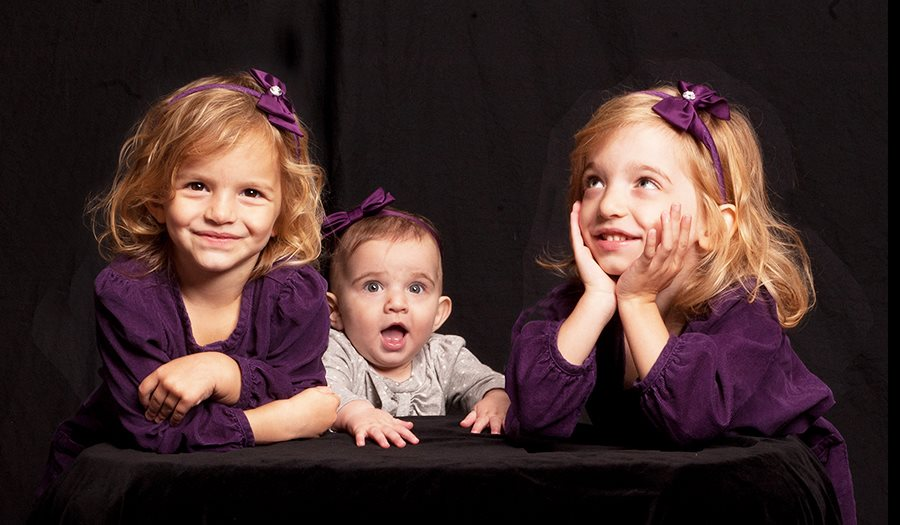 This is a composite of three images - one for each of the twins and the baby - all put together in Photoshop.