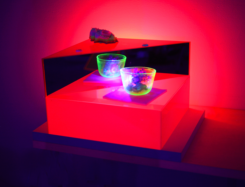 'Red Tide,' 2019. Plexiglass, mirror, UV LED light, uranium glass, and phosphorescent resin cast objects.