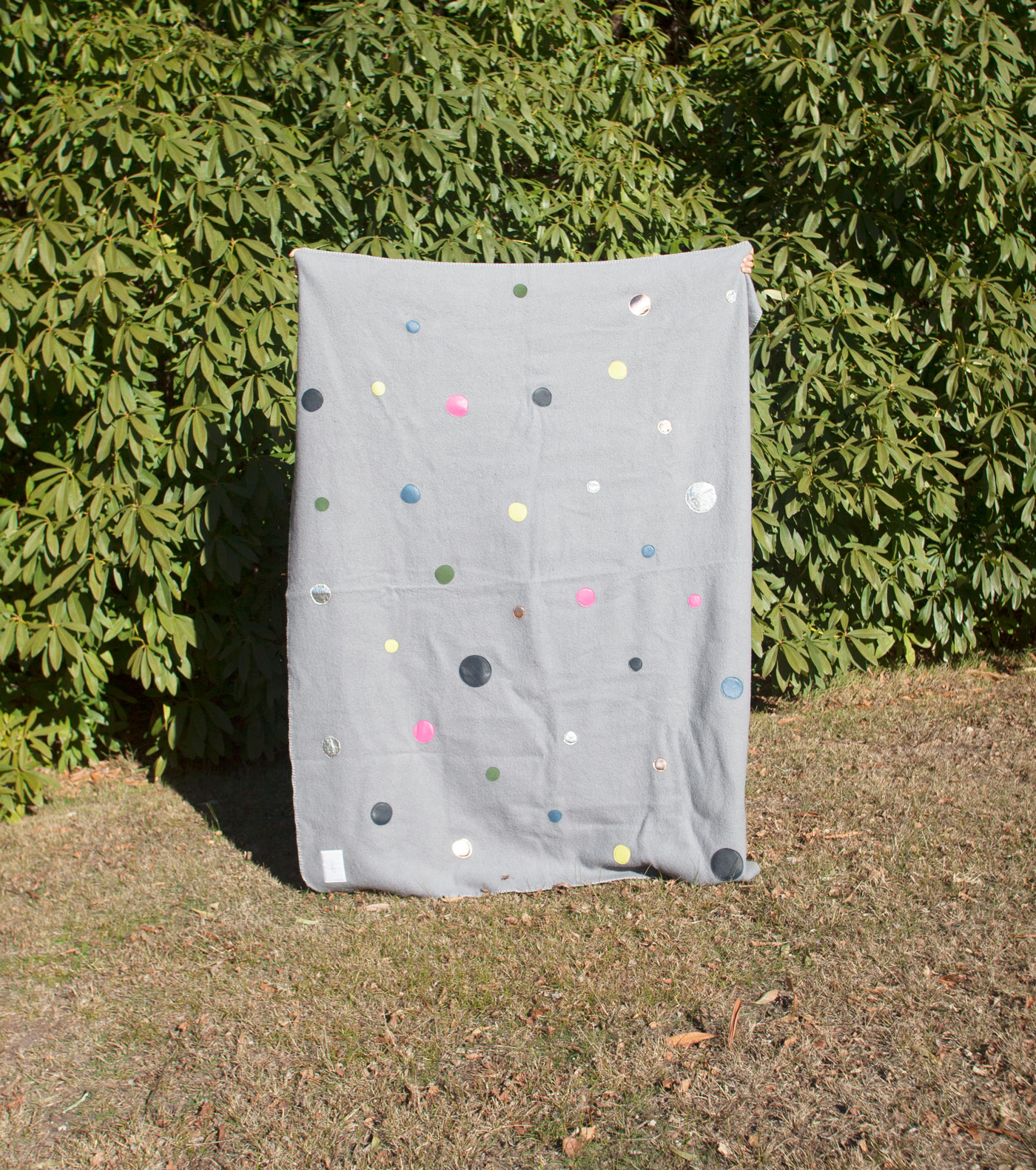 Bubbles Blanket - Bubbles is a Grey crafted Merino Wool blanket with leather detailing. This blanket is the perfect size for snuggling up on the couch, or an extra layer for your bed. It has a label on the back to write your name, to give it a personalised touch (and so you don't have to share if you don't want to).One of a kind, the shapes are made up of colourful leather pieces, all hand cut and sewn on by me.The blankets are sourced from Tasmania, Australia, and are super soft, hard wearing, and warm.Size: 175cm x 150cm