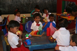 Tittagalla children eating special apples while exploring the new toys delivered to their pre-school from UK donations